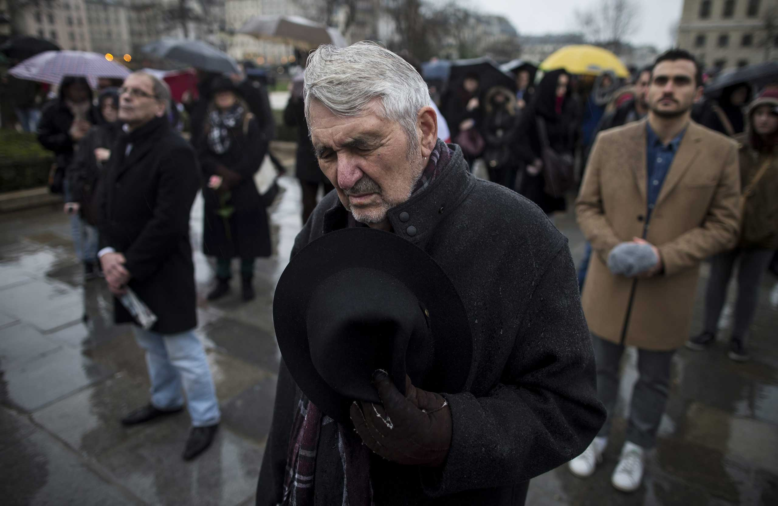 An older citizen removes his hat in a rain shower as he joins others gathered for a minute of silence in front of Notre Dame cathedral, Jan. 8, 2014.