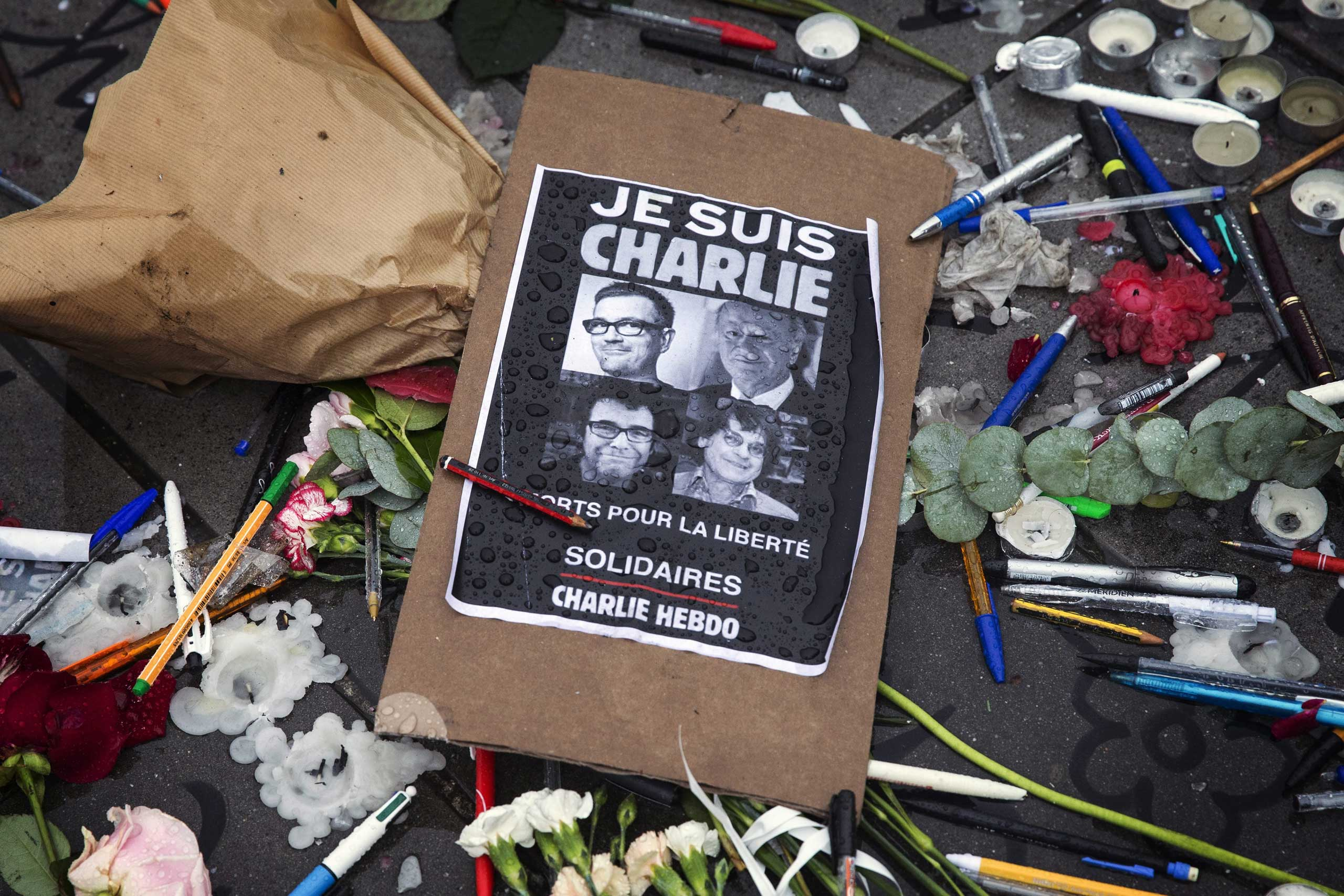A poster reads 'Je suis Charlie' (I am Charlie) amid symbolic pens and pencils on Place de la Republique as people gather for a minute of silence commemorating those killed in a shooting at French satirical magazine 'Charlie Hebdo', in Paris, Jan. 8, 2015.