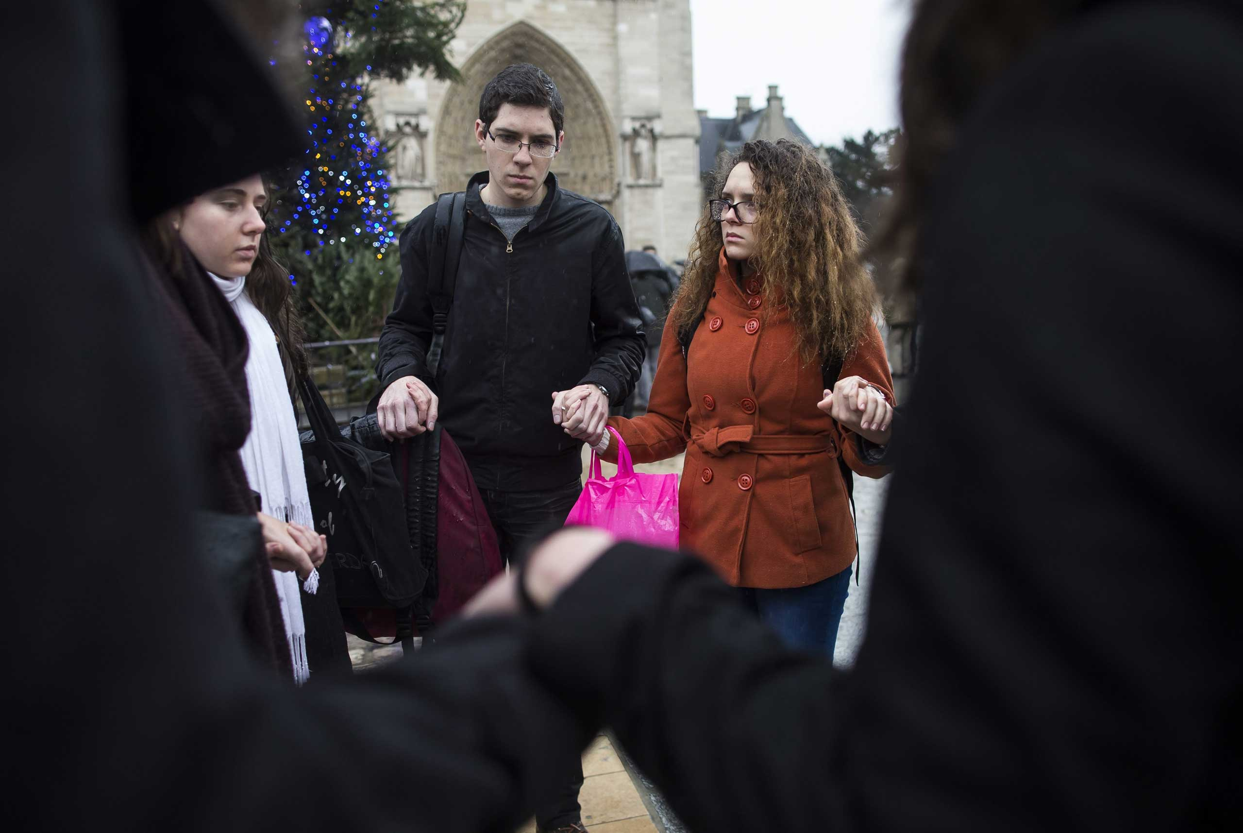 Young Parisians gather for a minute of silence in front of Notre Dame cathedral, Jan 8, 2014.