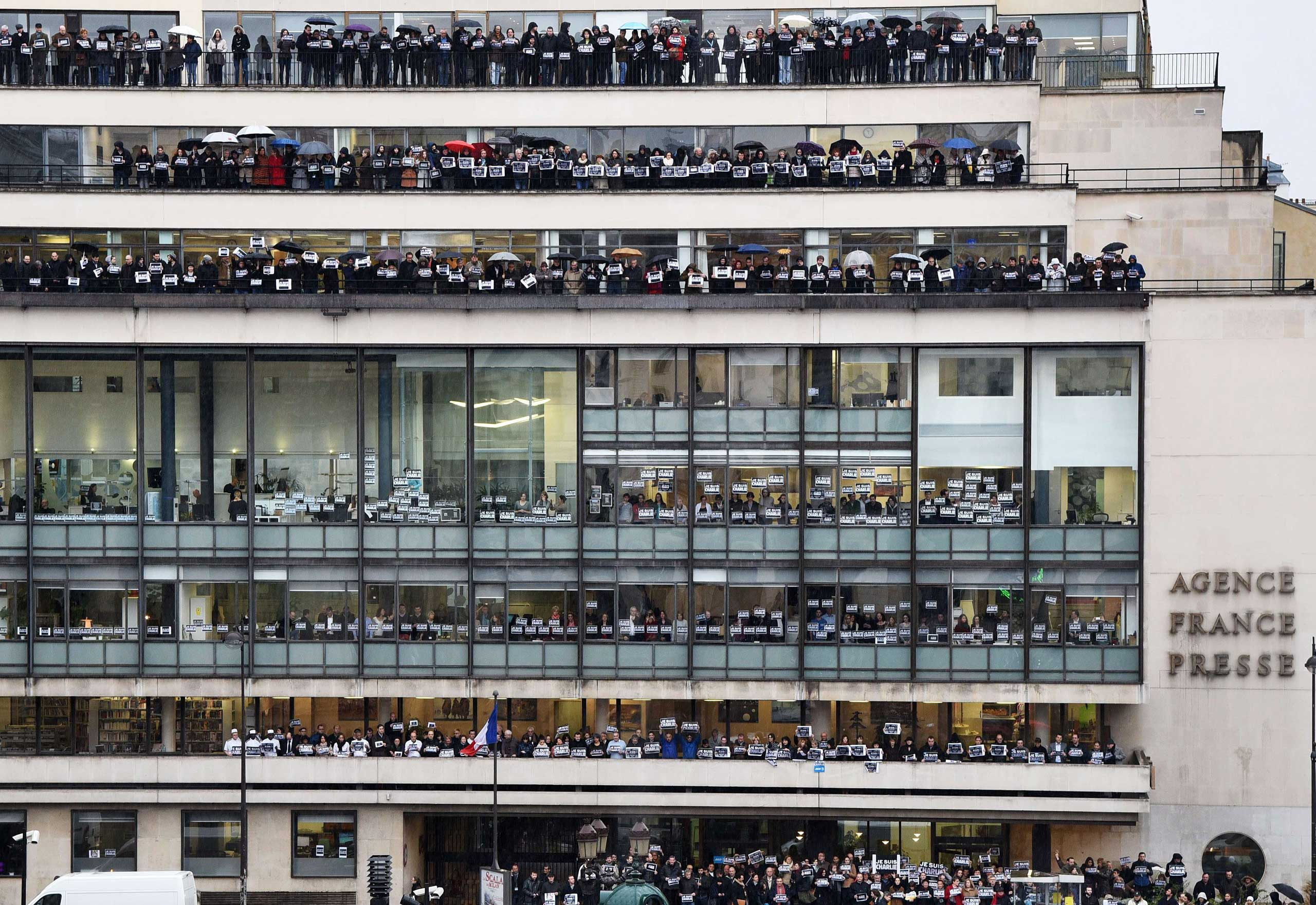 "Journalists of international press agency Agence France-Presse hold signs reading ""Je suis Charlie"" (I am Charlie) at their headquarters in Paris as they observe a minute of silence on Jan. 8, 2015."