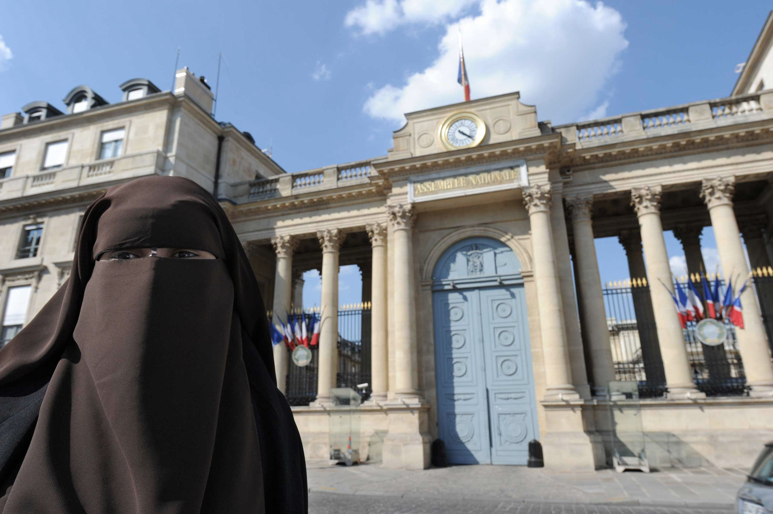 A woman poses in front of the French National Assembly to protest against ban on wearing full-face niqab veils in public, in Paris in 2011.