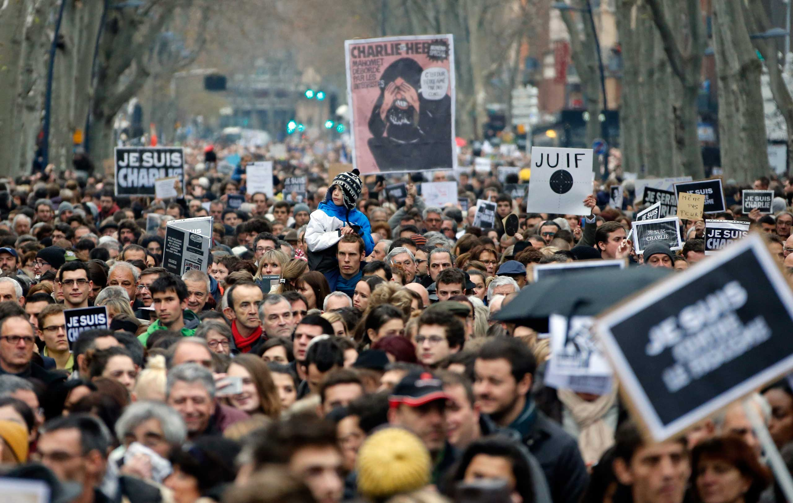 Thousands peoples walks during a  tribute to the victims of the attack on the Paris headquarters of French satirical magazine Charlie Hebdo, in Toulouse, Jan. 10, 2014.