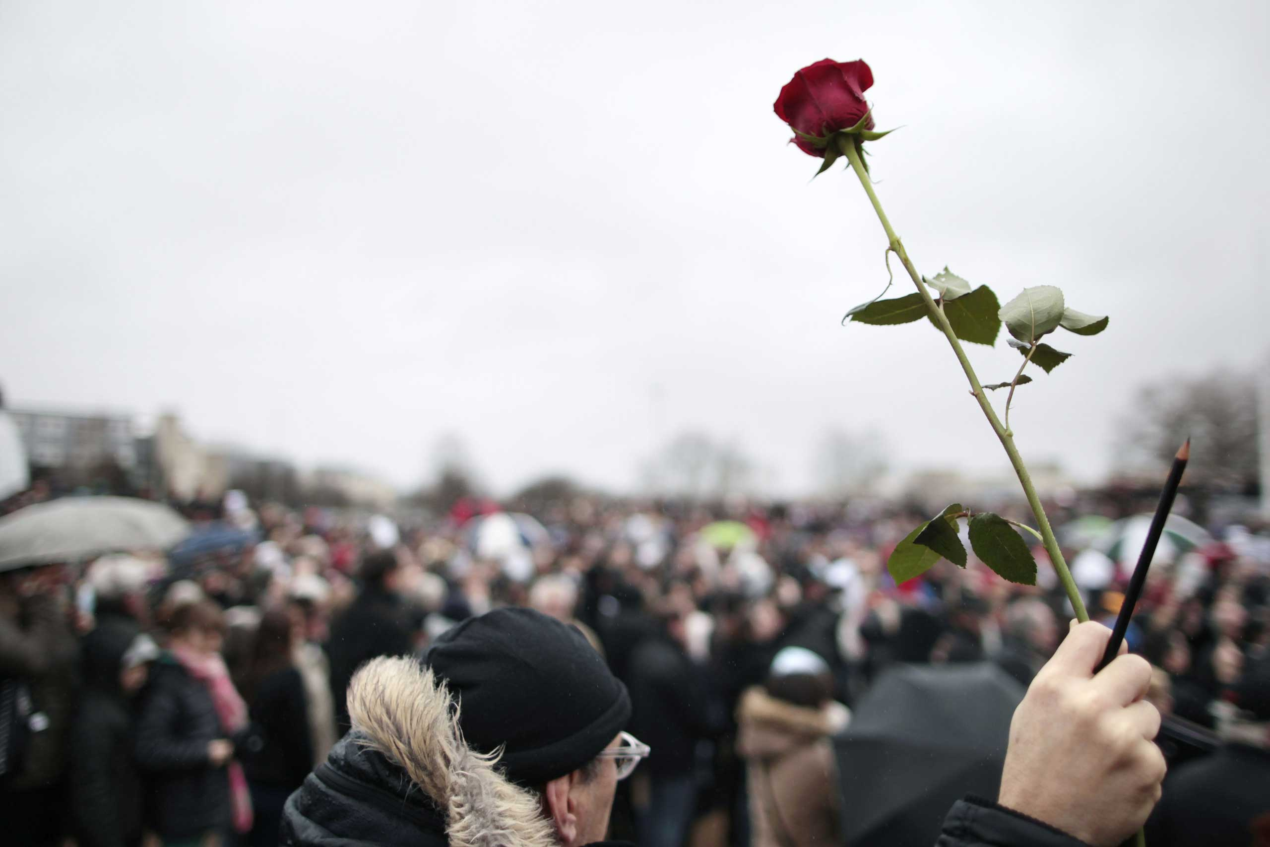 A man hold a rose and pencil during a rally at the Memorial Square in Caen on Jan. 10, 2015.