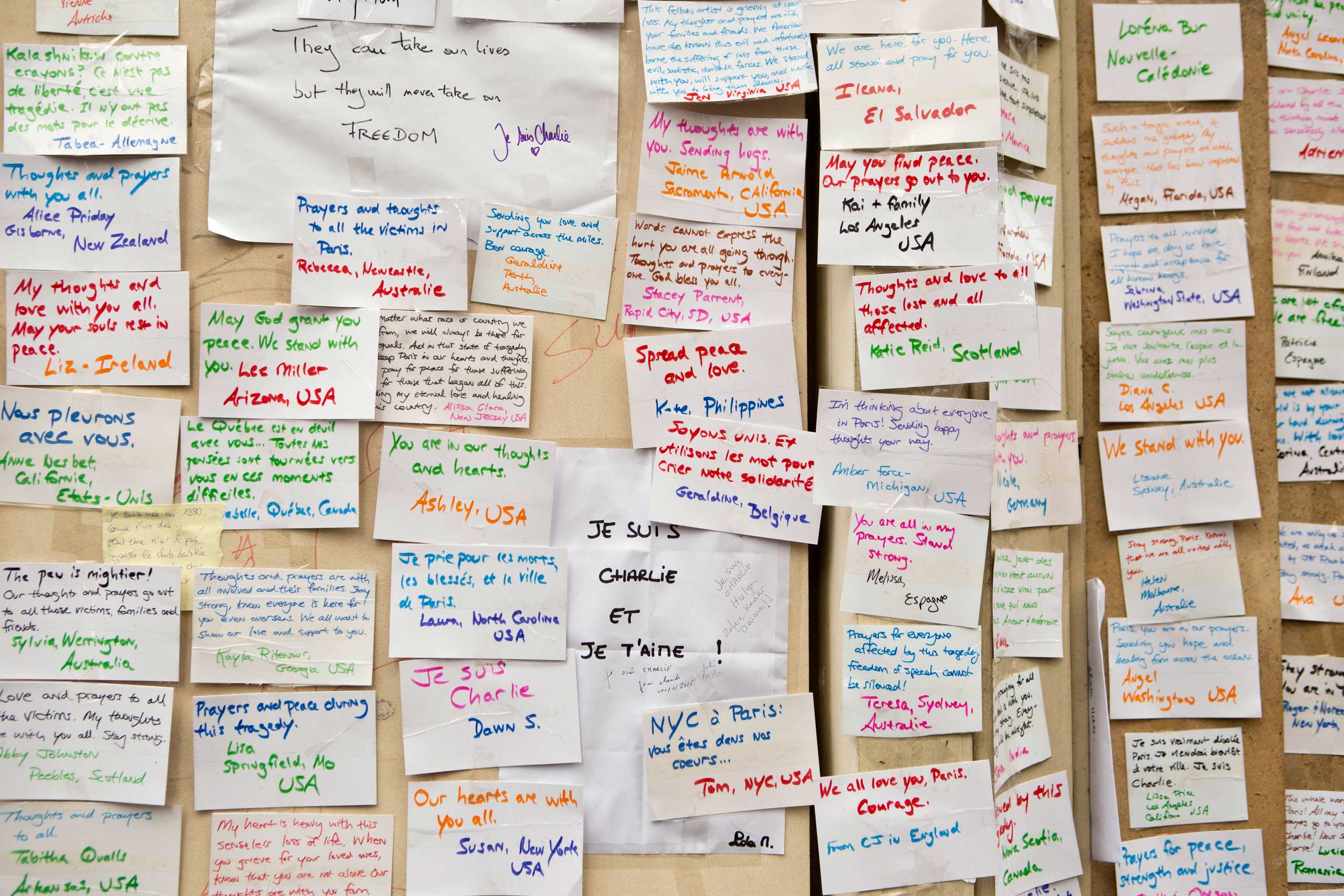 Messages left by people visiting a makeshift memorial are pasted to a wall near the offices of French satirical newspaper Charlie Hebdo in Paris, Jan. 10, 2015.