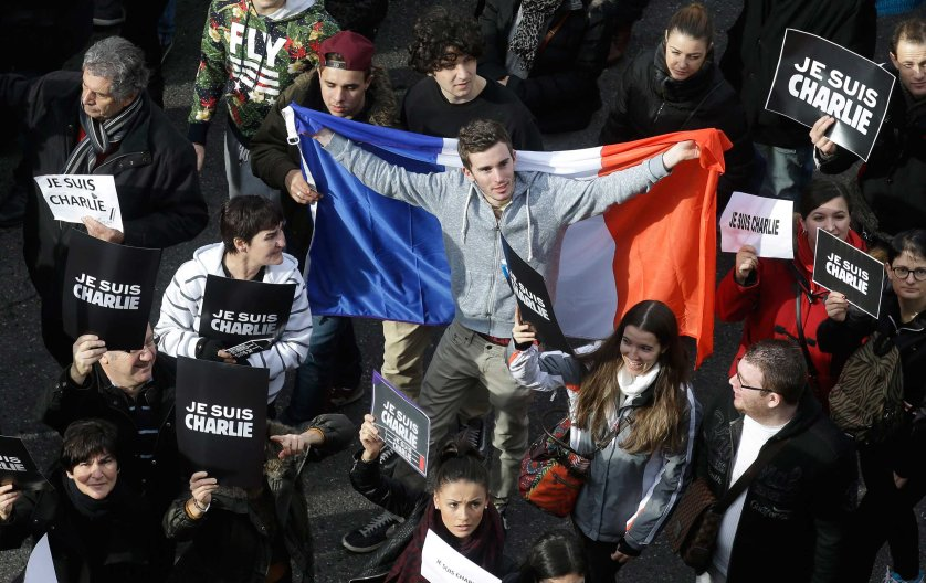 A man holds a French flag during a silent walk for victims of the shooting at the satirical newspaper Charlie Hebdo, Jan. 10, 2015, in Nice.