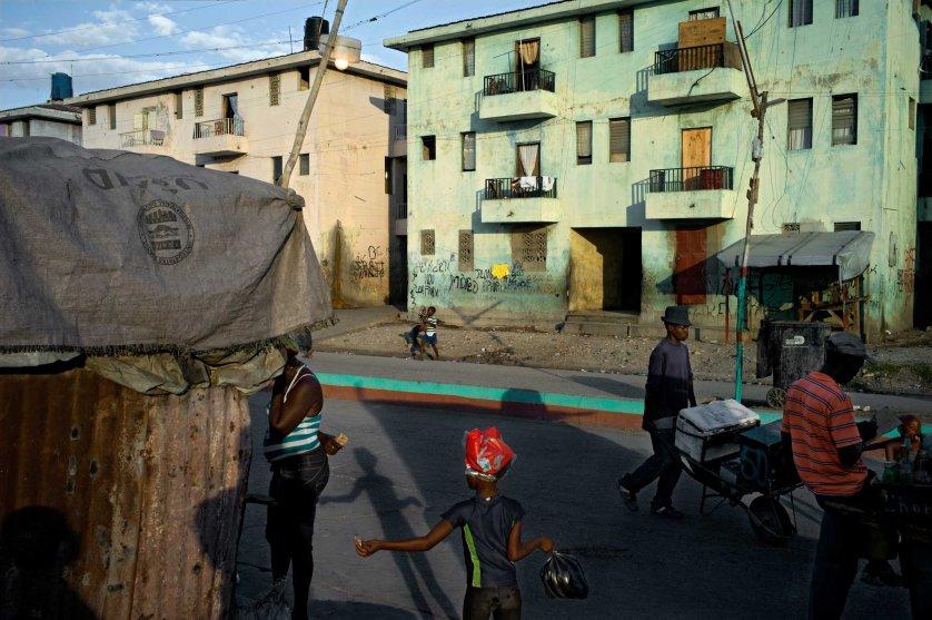 """Port-au-Prince, Haïti, 14 January 2014The ''La Salinne'' destrict has been set up by former President J-B Aristide. This estate, unique in the city, is still a bastion of the Aristide's partisans. Many former leaders and members of the ''Chimères'' – gang in Aristide's service- live and hide here since the police are looking for them. Unemployment and the lack of business are all the more noticeable since the State has no plan for this area supporting the opposition.Le quartier """"La Salinne"""" a été aménagé par l'ancien président J-B Aristide. Cette cité, unique dans la capitale, reste un bastion pro-Aristid et de nombreux anciens chefs et membres des Chimères (gangs aux services pu Parti de Arisitde pendant son pouvoir) y habitent et s'y cachent puisqu'ils sont recherchés par la police. Le chômage et le manque d'activités économiques sont criants puisque l'état ne développe aucun projet dans cette zone de la ville qui soutien l'opposition."""