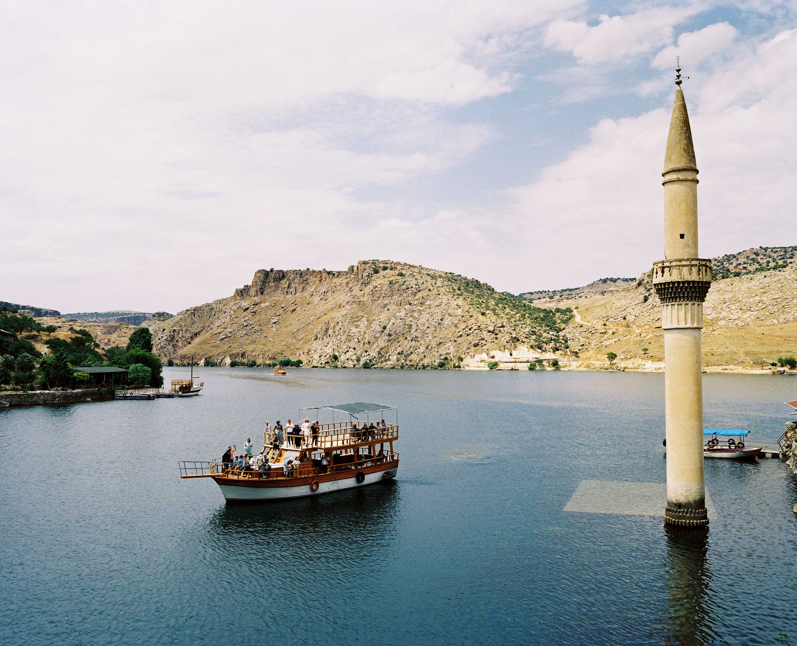 A tourist boat visits the former village of Savaçan, flooded by the reservoir lake of the Birecik Dam on the Euphrates River. Turkey.