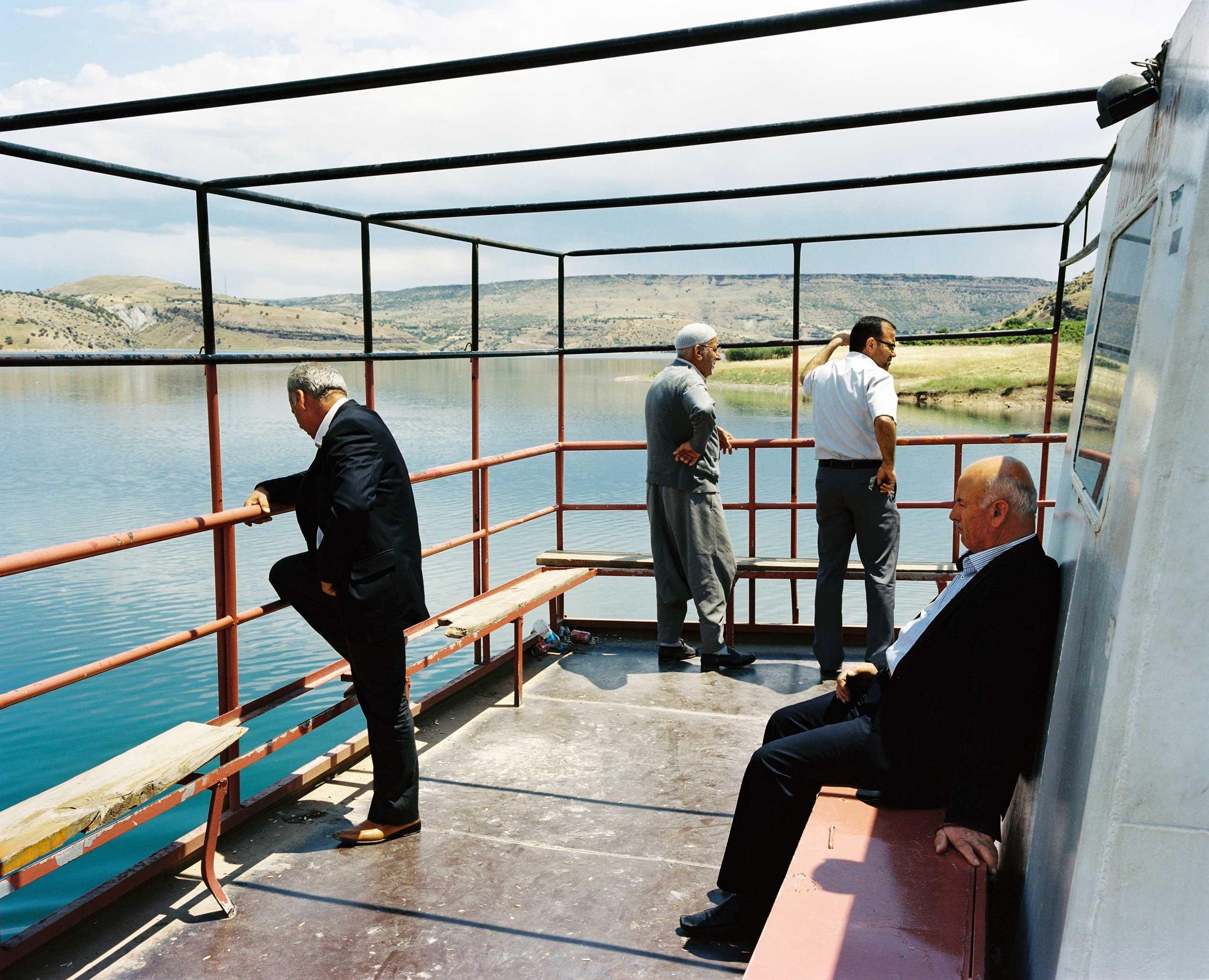 Men on a ferry boat travel across the Euphrates River near the Keban Dam. Keban, Turkey.