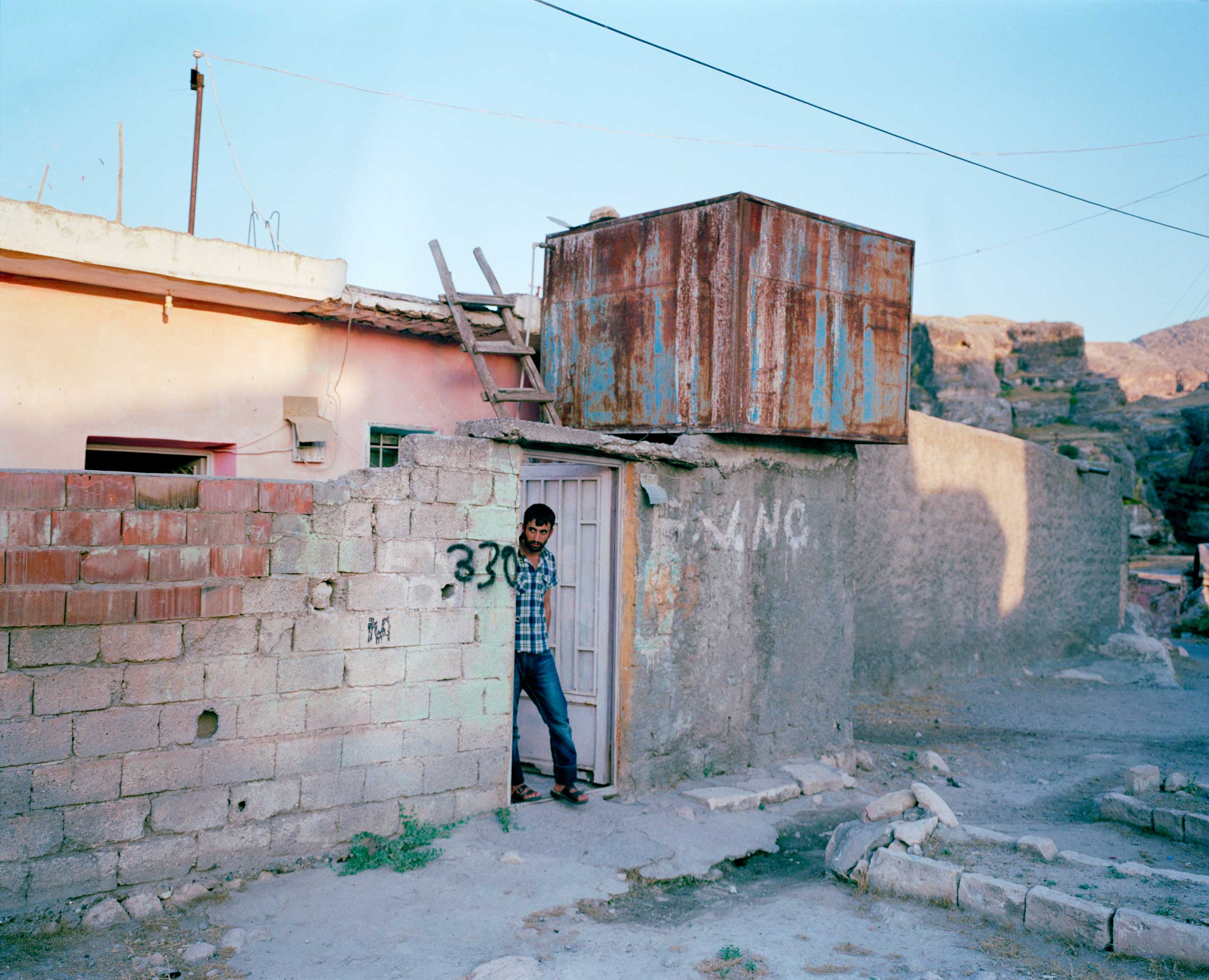 A man steps out of his home one evening. The number written on the side is for the municipality to know which house belongs to whom, so it can financially compensate the owners. Hasankeyf, Turkey.