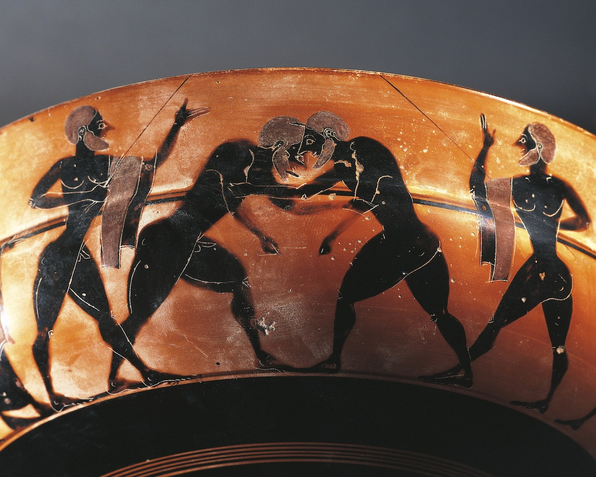 An ancient Greek cup with a gymnasium scene  with two referees and two wrestlers