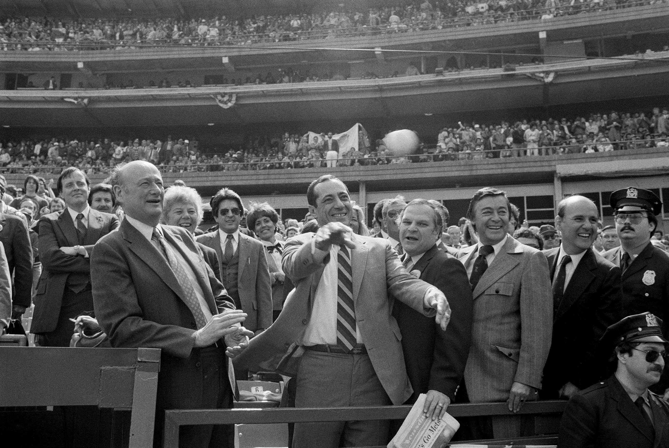 Gov. Mario Cuomo, with some coaching by Mayor Ed Koch, left, throws out the first pitch at Shea Stadium, before a New York Mets game in New York City on April 5, 1983.
