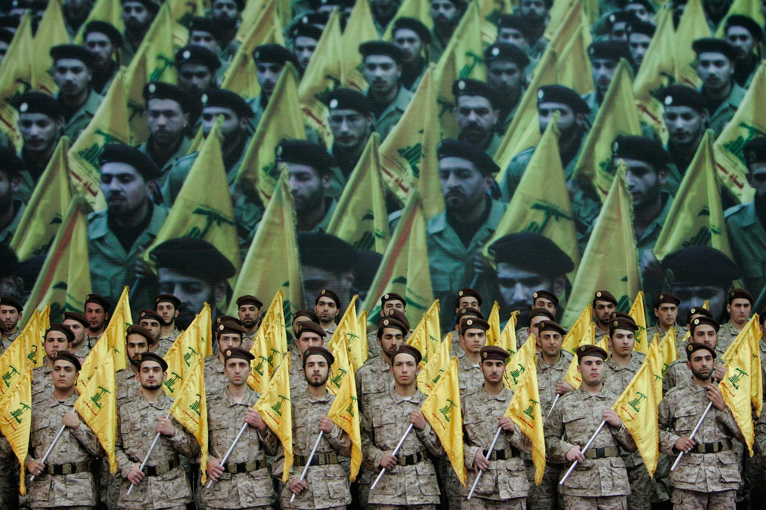 Hezbollah fighters hold their party flags as they attend a rally to commemorate slain top Hezbollah commander Imad Mughniyeh and two other leaders, Abbas Musawi and Ragheb Harb, in the Shiite suburb of Beirut, Feb. 22, 2008.