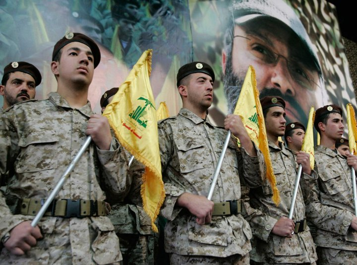 Hezbollah fighters hold their party flags and stand next to a portrait which shows their slain top commander Imad Mughniyeh, as they attend a rally to commemorate Mughniyeh and two other leaders, Abbas Musawi and Ragheb Harb, in the Shiite suburb of Beirut, Feb. 22, 2008.