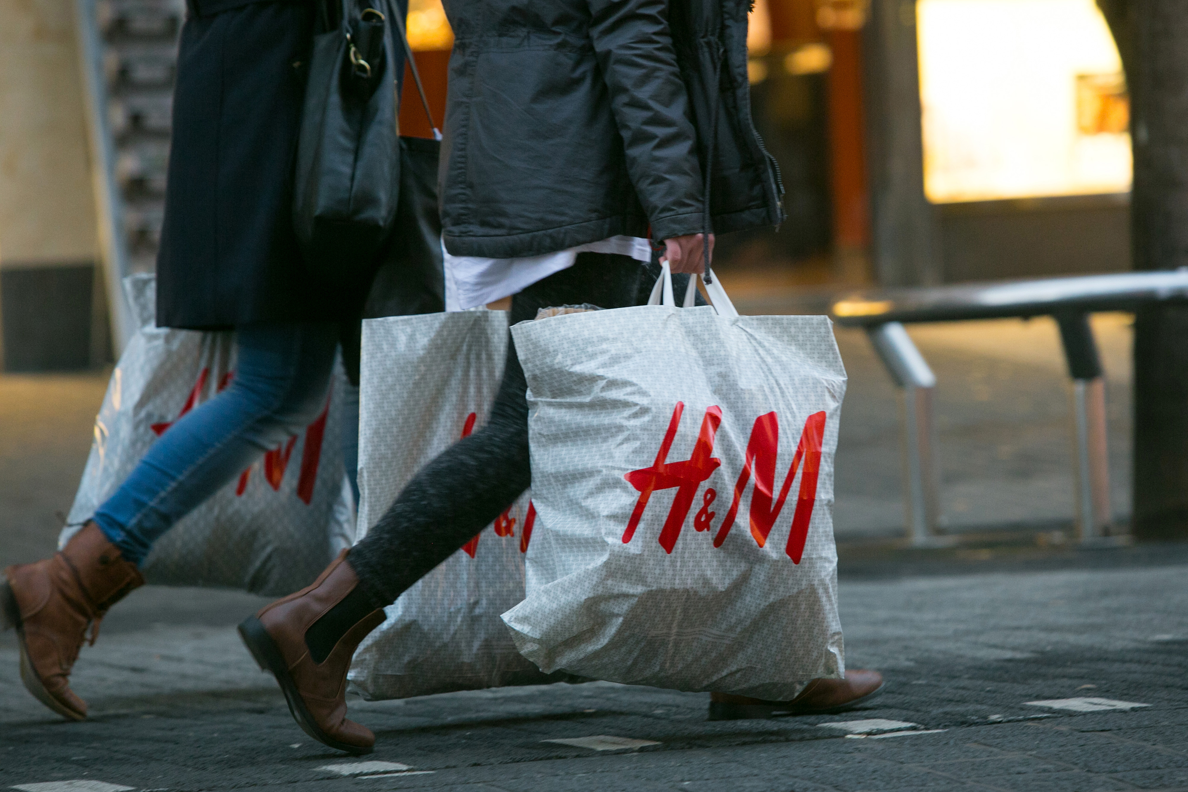 Pedestrians carry Hennes & Mauritz AB (H&M) branded shopping bags in Mannheim, Germany, on Tuesday, Jan. 20, 2015.