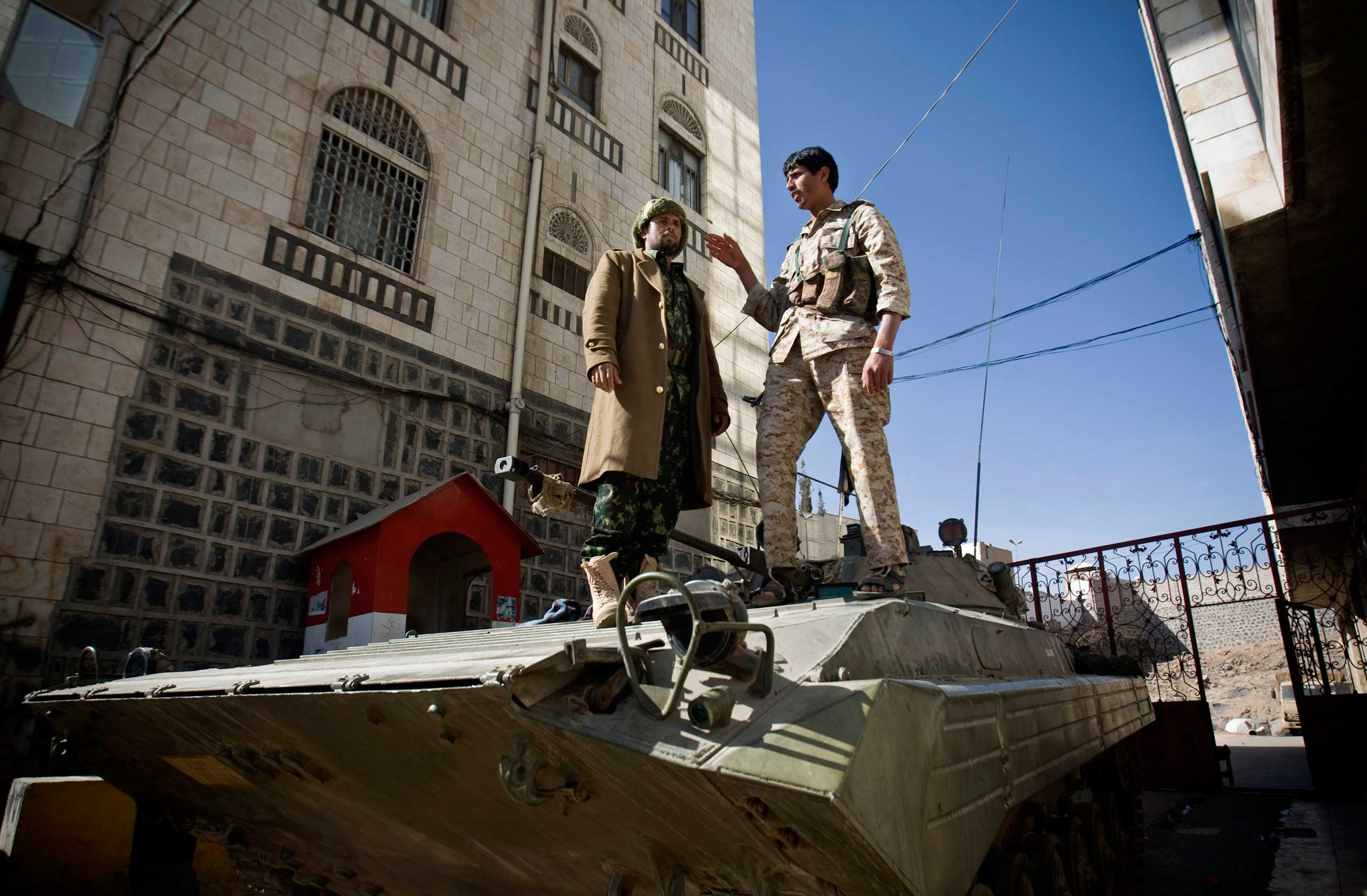 Houthi Shiite Yemeni wearing army uniforms stand atop an armored vehicle, which was seized from the army during recent clashes, outside the house of Yemen's President Abed Rabbo Mansour Hadi in Sanaa, Yemen, Jan. 22, 2015.