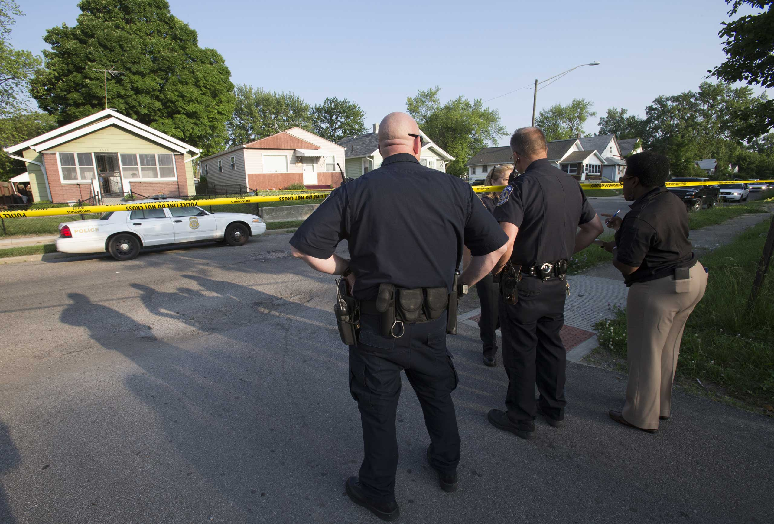 Indianapolis Metropolitan Police Department officers work  on Indianapolis' Eastside after an officer was injured in in an exchange of gunfire that killed the suspect on May 30, 2014.
