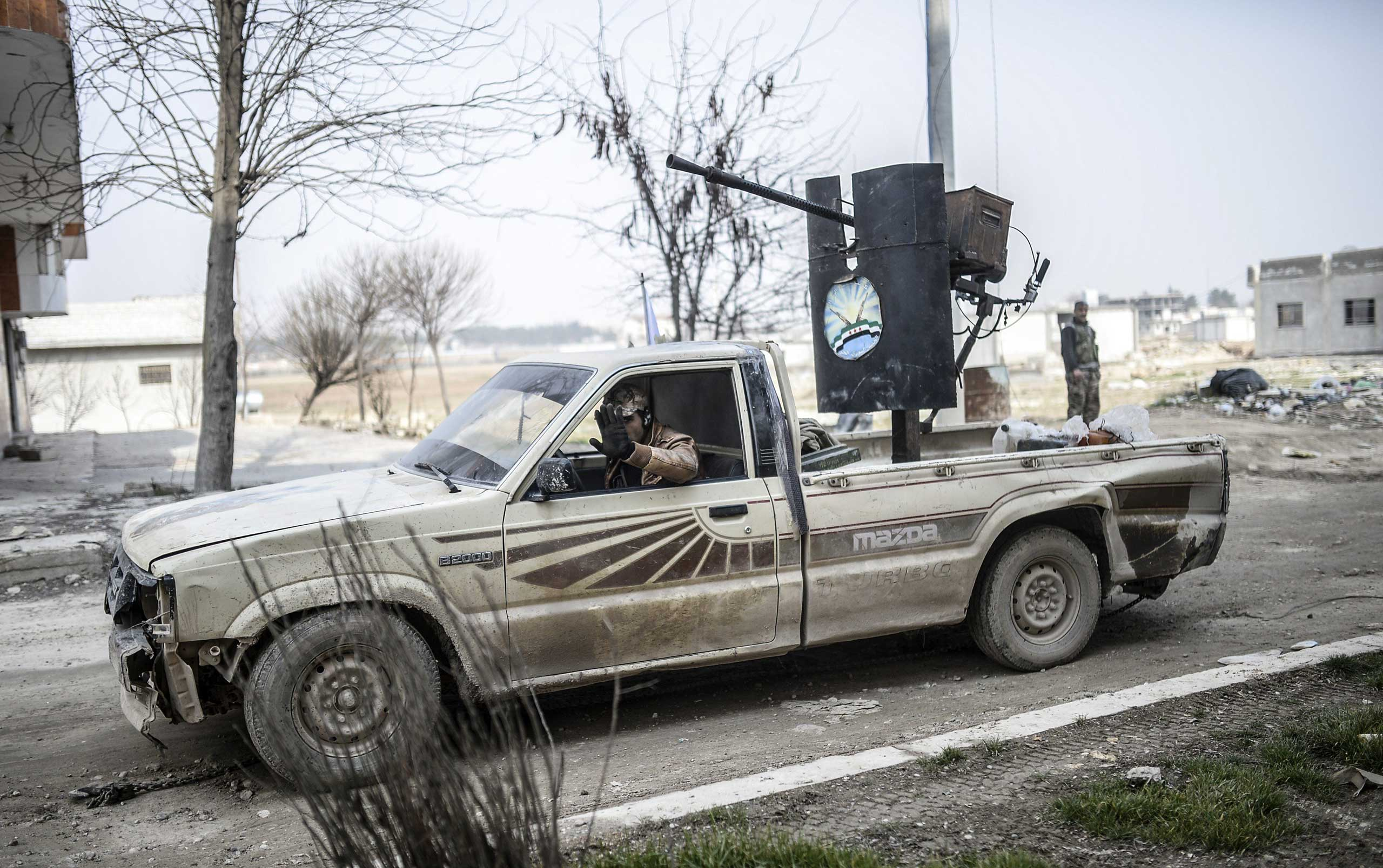 A Kurdish fighter drives a truck with a heavy gun machine in the center of the Syrian town of Kobani on Jan. 28. 2015.