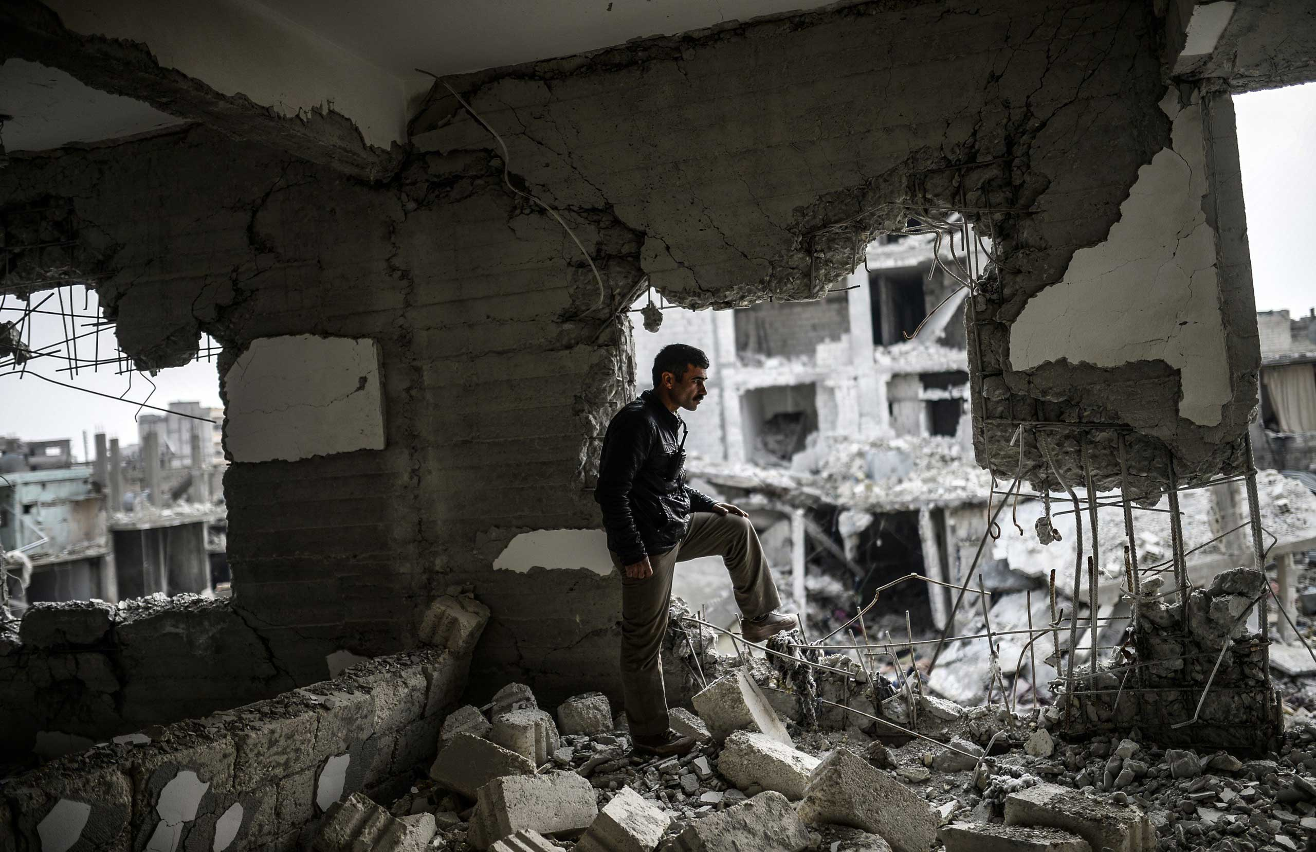 A Kurdish man stands in a destroyed building in the center of the Syrian border town of Kobani on Jan. 28, 2015.