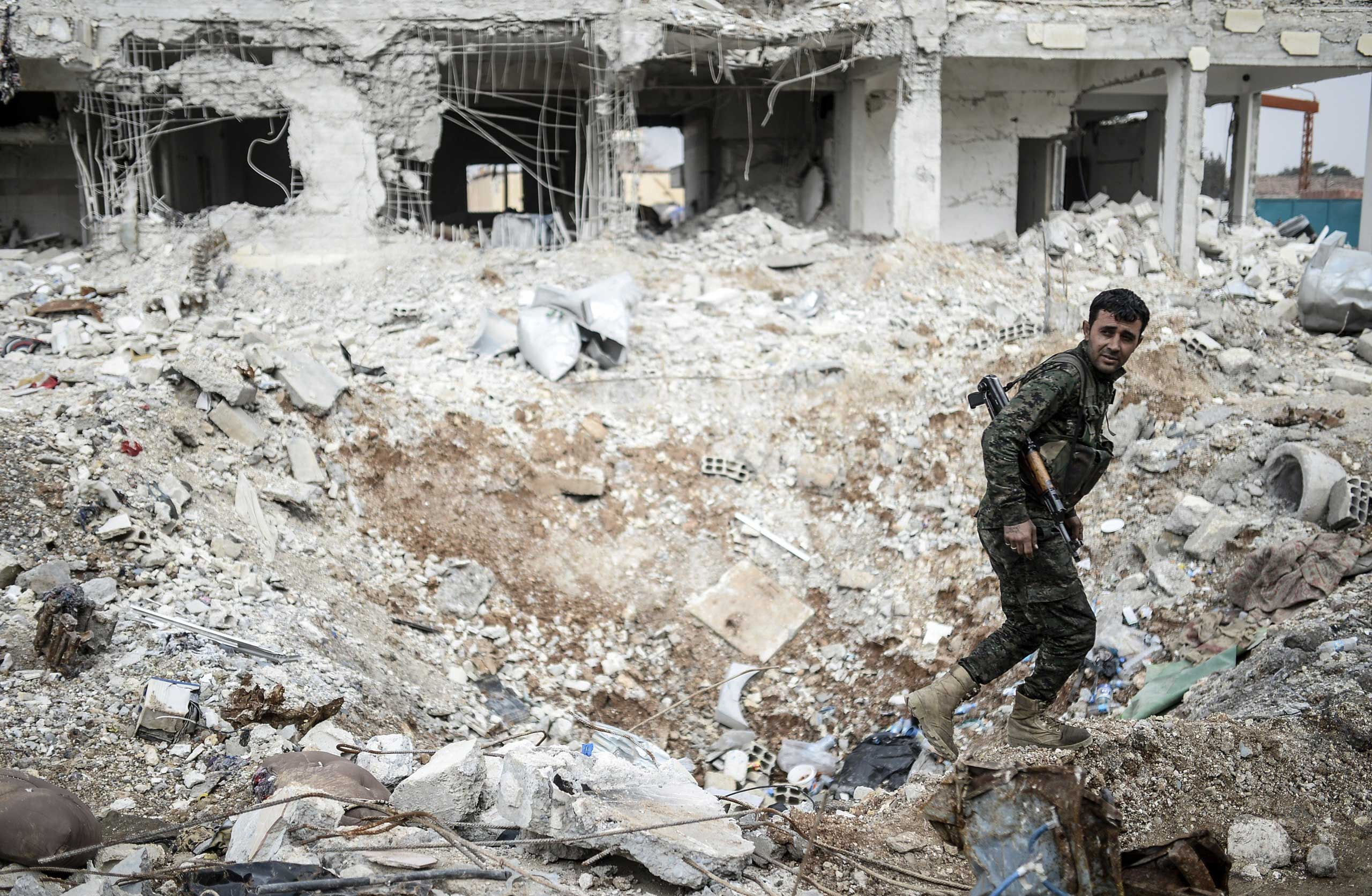 A Kurdish fighter walks through the wreckage of a building in the center of the Syrian town of Kobani on Jan. 28. 2015.