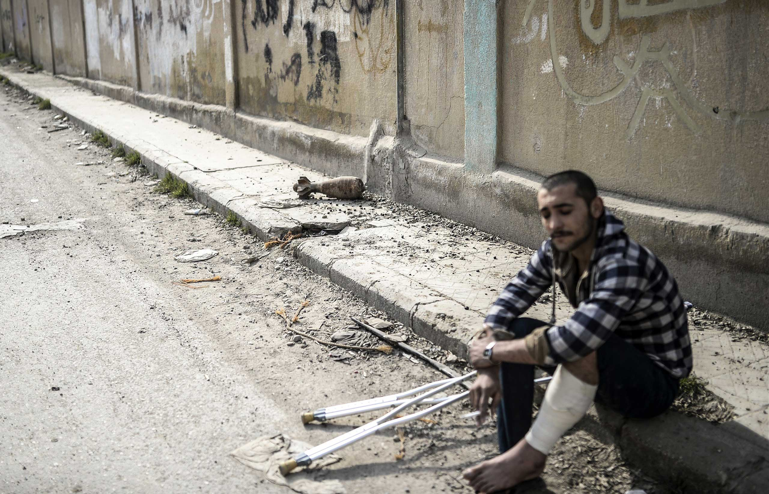 An injured Kurdish fighter sits near the site where a projectile landed in the center of the Syrian town of Kobani on Jan. 28, 2015.