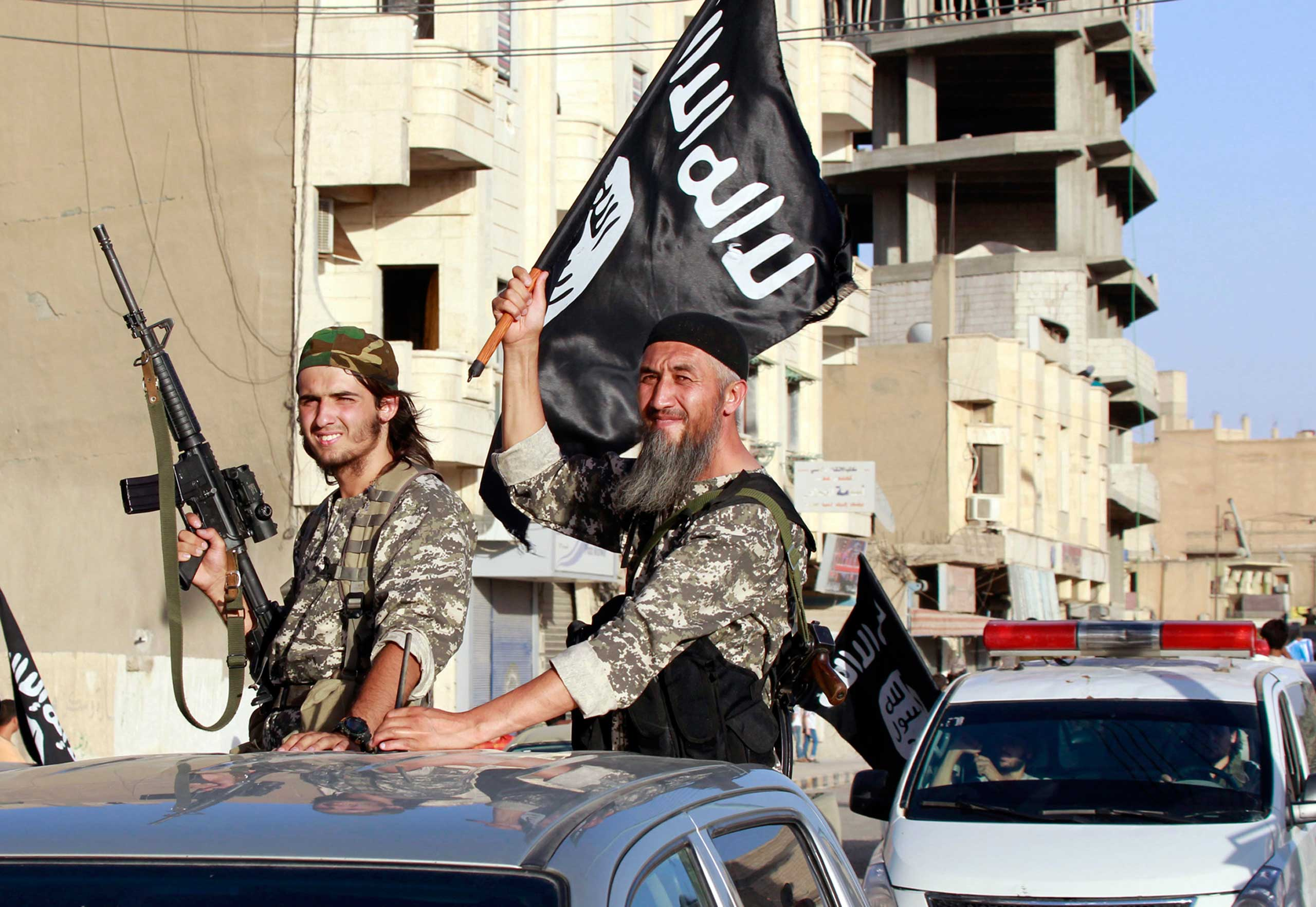 Militant Islamist fighters wave flags as they take part in a military parade along the streets of Syria's northern Raqqa province in Syria, June 30, 2014.
