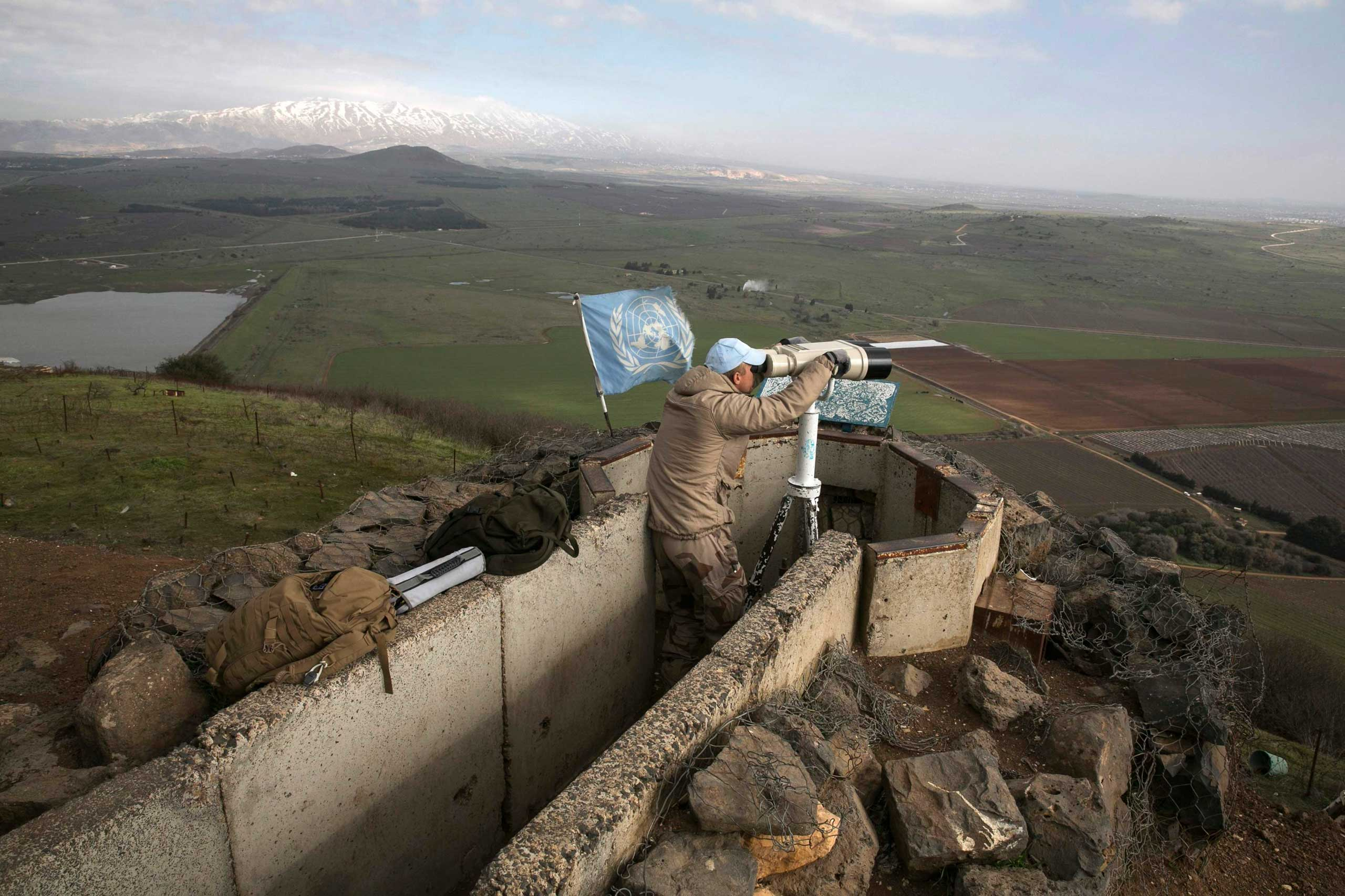 A member of the United Nations Disengagement Observer Force looks through binoculars at Mount Bental, an observation post in the Israeli occupied Golan Heights, Jan. 28, 2015.