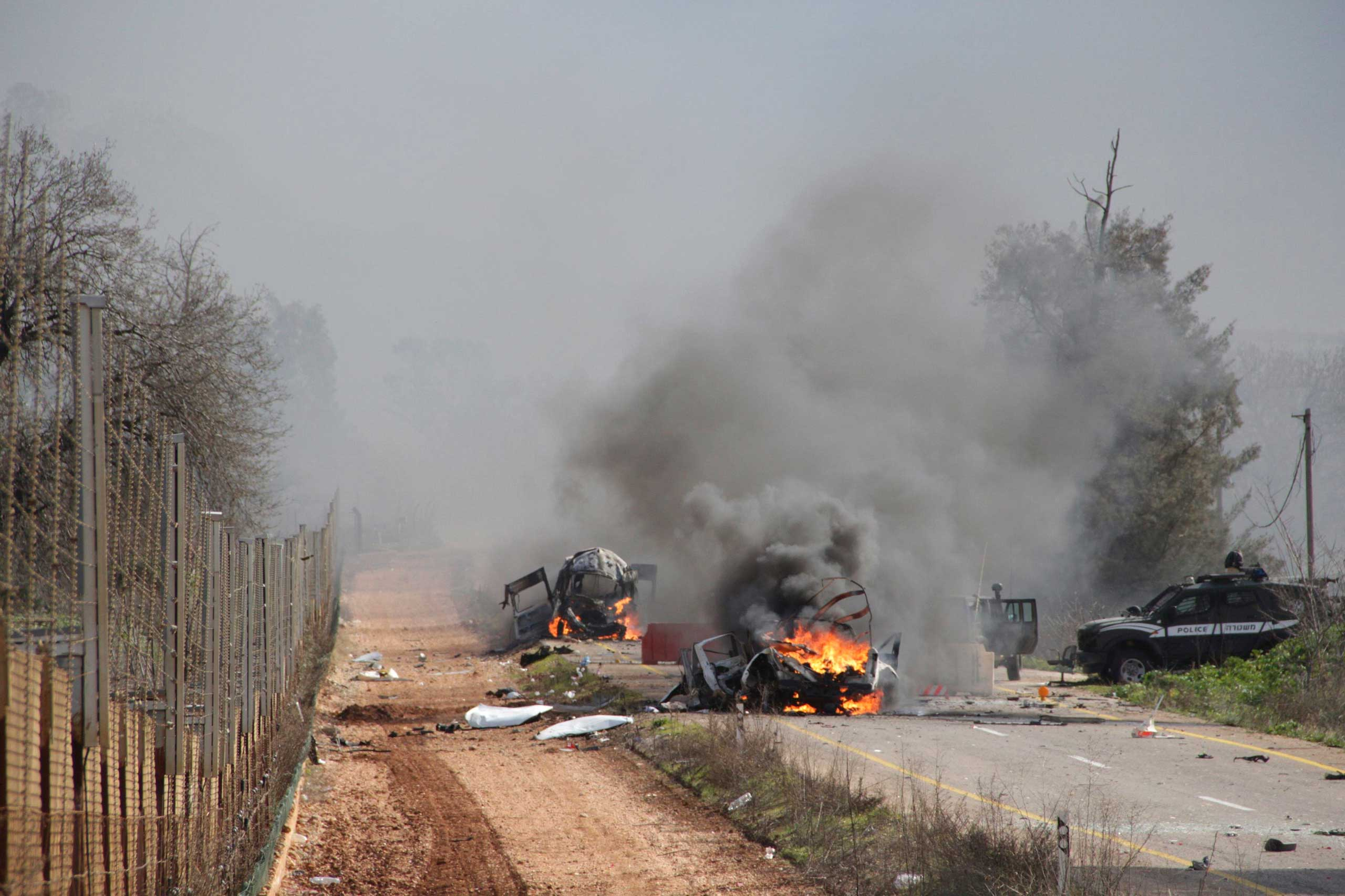Burning vehicles are seen near the village of Ghajar on Israel's border with Lebanon, Jan. 28, 2015.