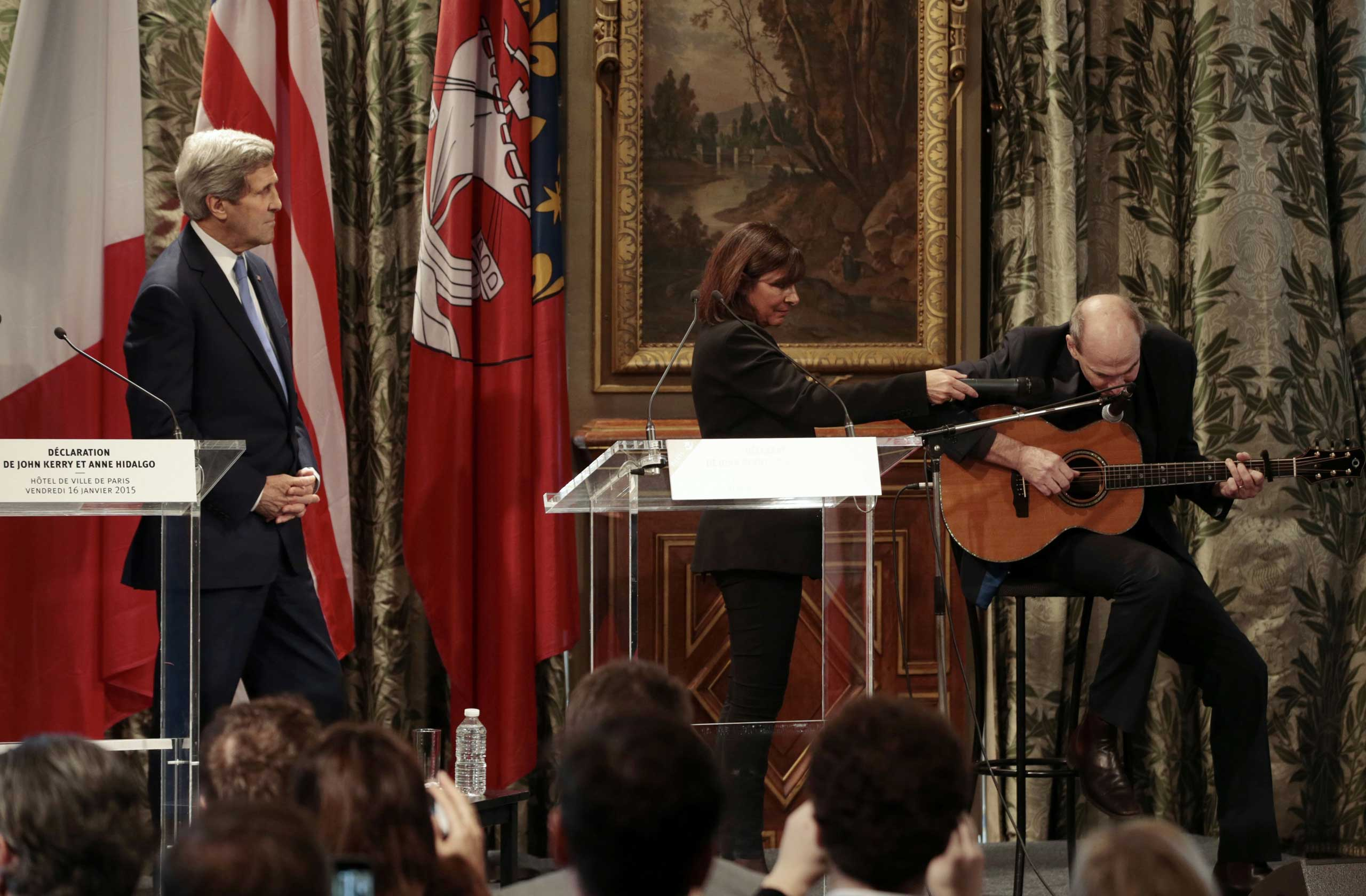 Paris Mayor Anne Hidalgo (C) and US Secretary of State John Kerry (L) listen to US musician James Taylor at Paris City Hall on January 16, 2015.