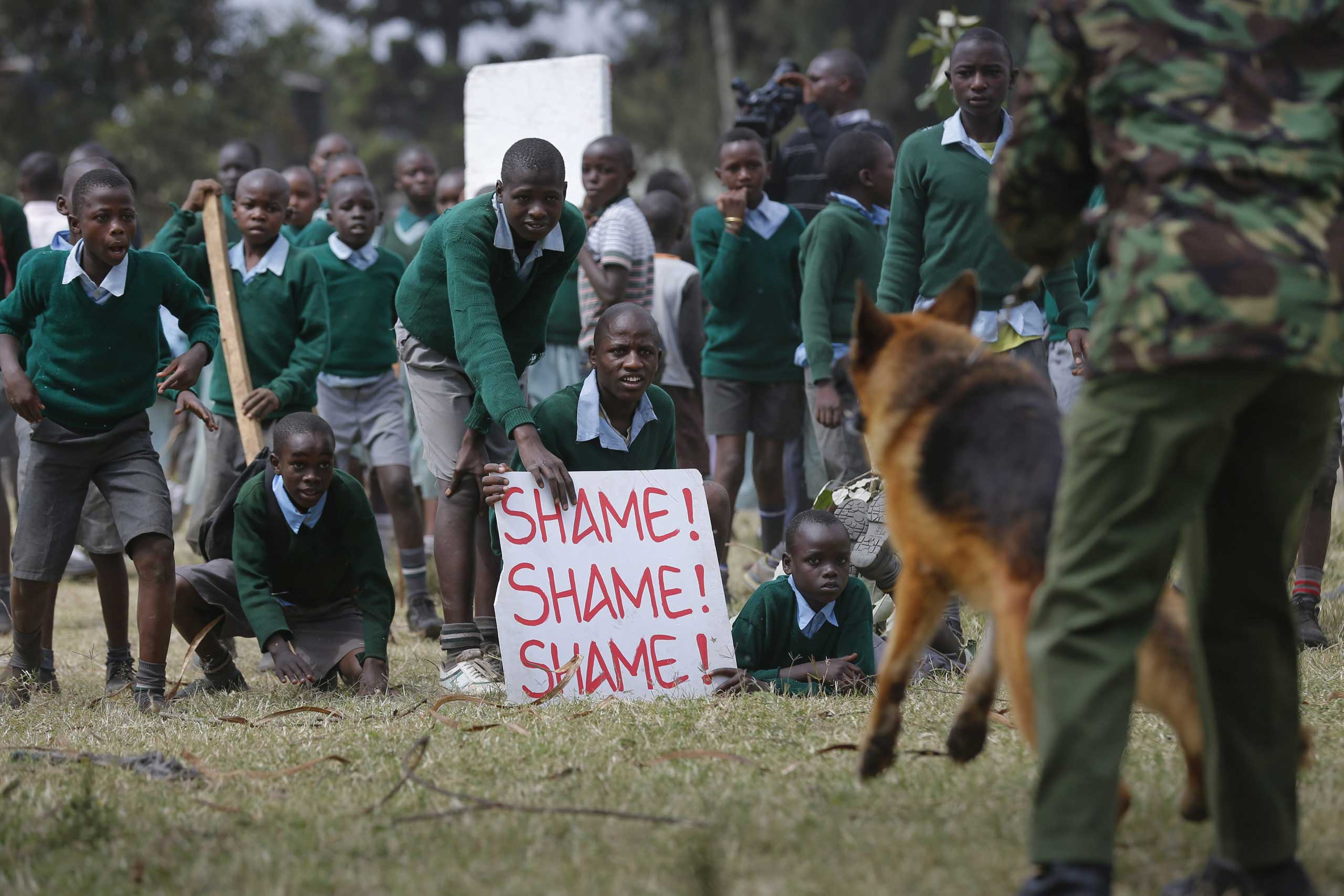 School children face off against a police dog handler during a protest against alleged land grabbing at Langata Road Primary School in Nairobi, Jan. 19 2015.