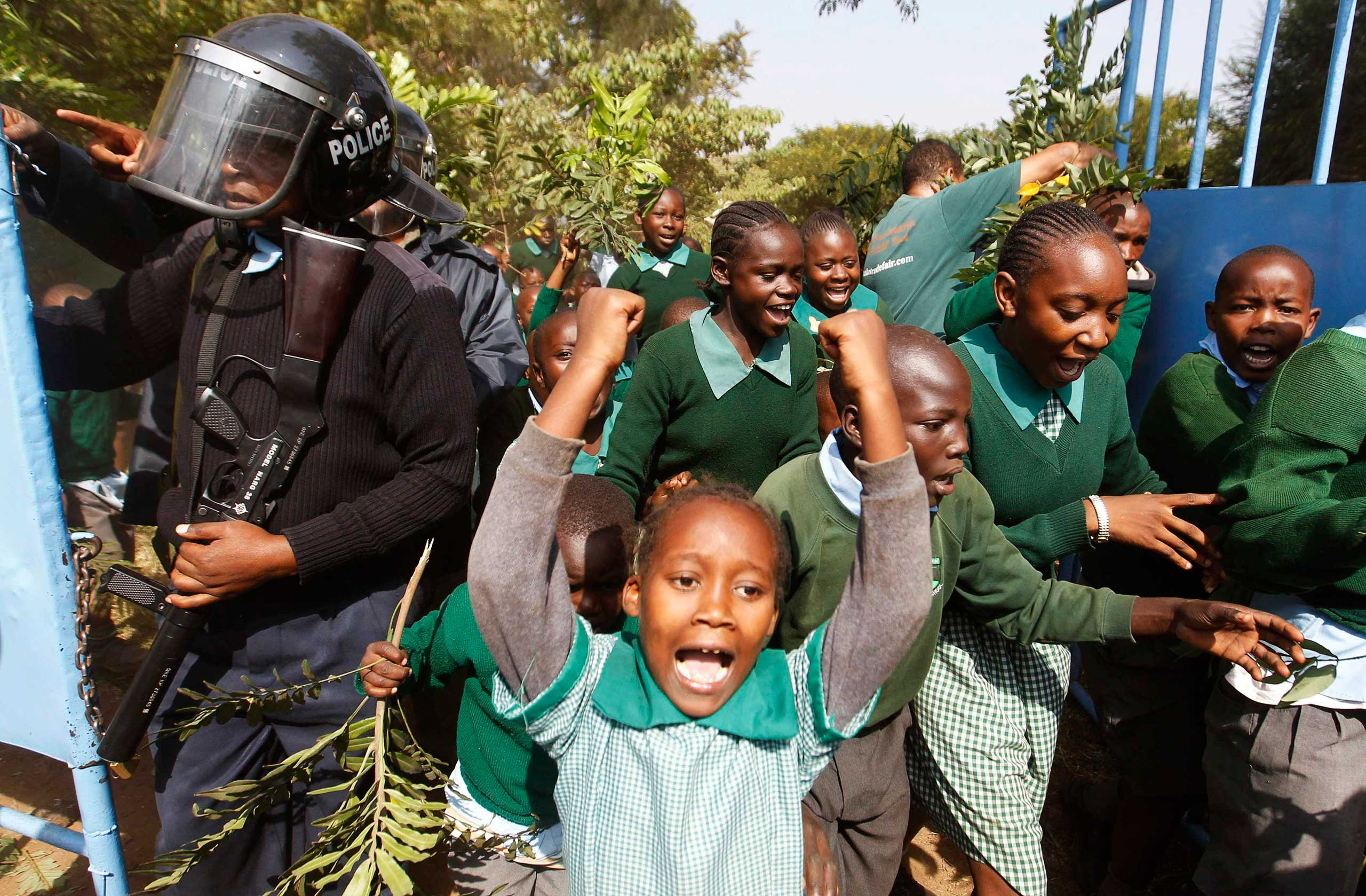 Students from Langata Primary School run past riot police as they protest against a perimeter wall illegally erected by a private developer around their school playground in Nairobi,  Jan. 19, 2015.