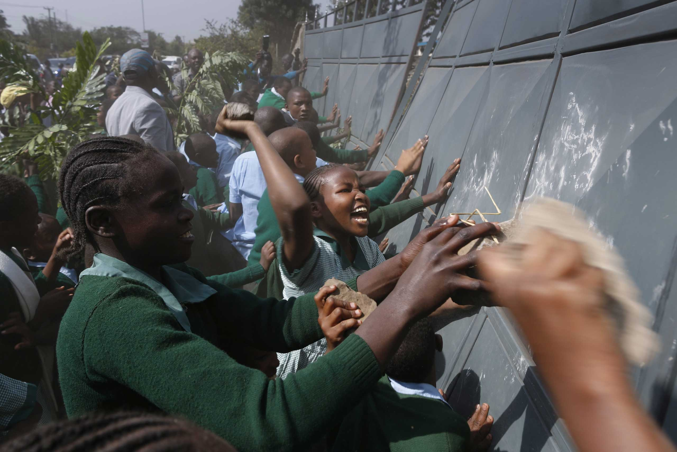 School children push the fence to enter the school playground during a protest against alleged land grabbing at Langata Road Primary School in Nairobi, Jan. 19, 2015.