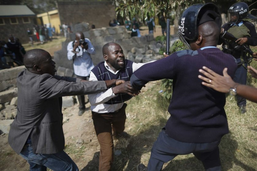 A protester clashes with a police officer during a protest against alleged land grabbing at Langata Road Primary School in Nairobi, Jan. 19, 2015.