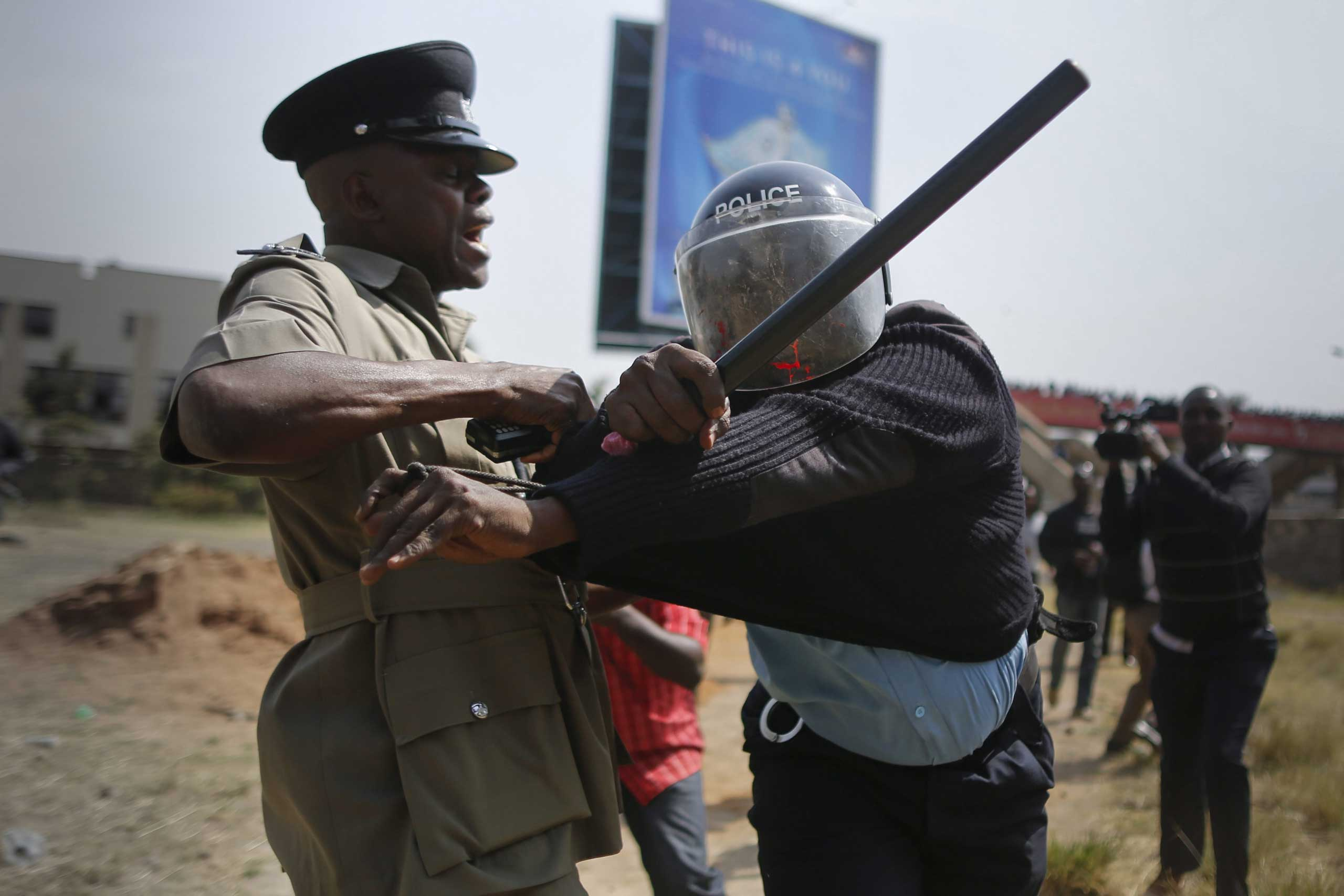 A police officer reacts as his colleague tries to calm him down after he was hit by a rock thrown by a protester during a protest against alleged land grabbing at Langata Road Primary School in Nairobi, Jan. 19, 2015.