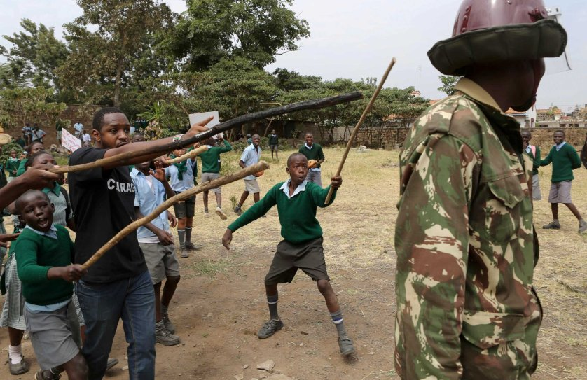 Kenyan school pupils and activists challenge riot police during a protest against the removal of their school's playground, at the Langata Road Primary School, in Nairobi, Jan. 19, 2015.