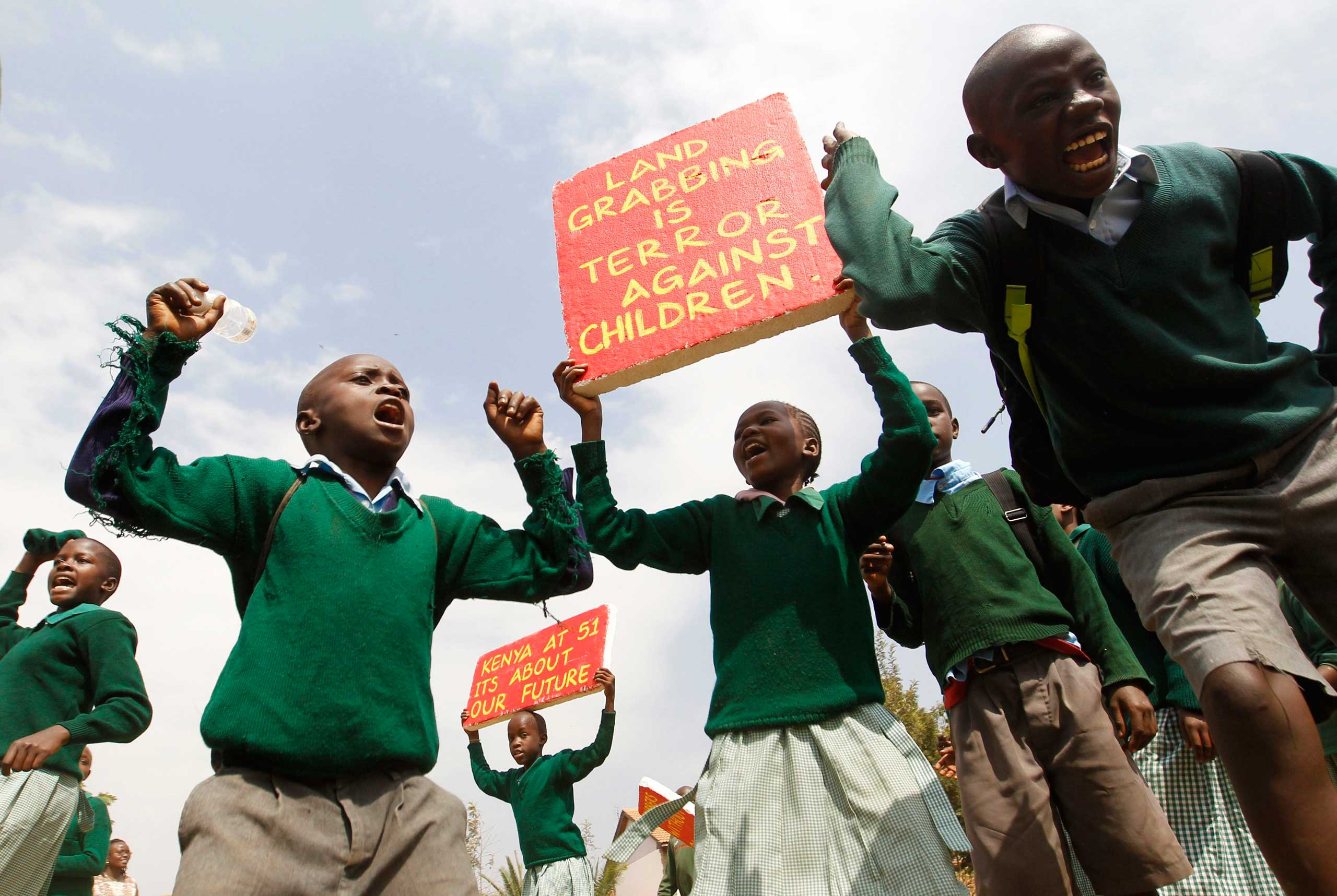 Students from Langata Primary School hold placards as they protest against a perimeter wall illegally erected by a private developer around their school playground in Kenya's capital Nairobi, Jan. 19, 2015.