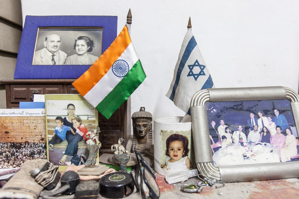 Family photographs, Indian and Israeli flags at the Cohen residence.