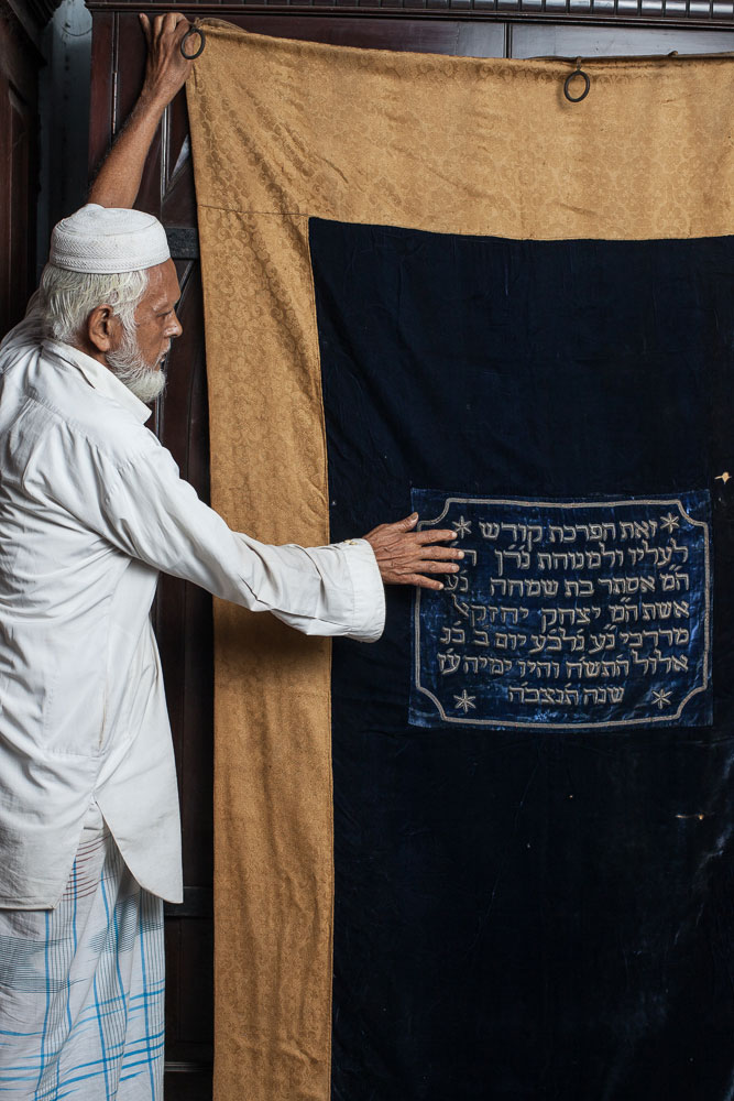 Sk. Nassir, 75, is one of the two Muslim caretakers of the Beth El Synagogue. Here he holds one of the parokhets (Torah ark curtains) that once hung inside the synagogue in August 2014.