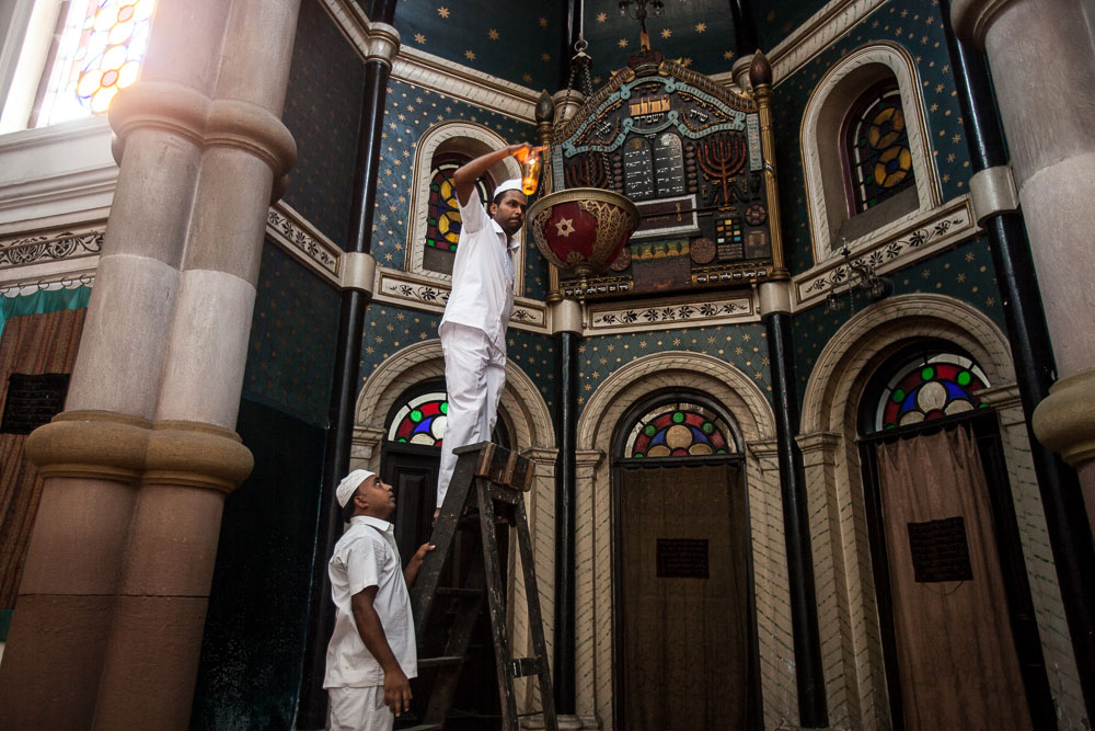Nrusingha Charan Swain and Anwar Khan, one of the four caretakers of the Maghen David synagogue, lighting the Ner Tamid inside the ark in August 2014.  Nrusingha is Hindu and Anwar is Muslim.