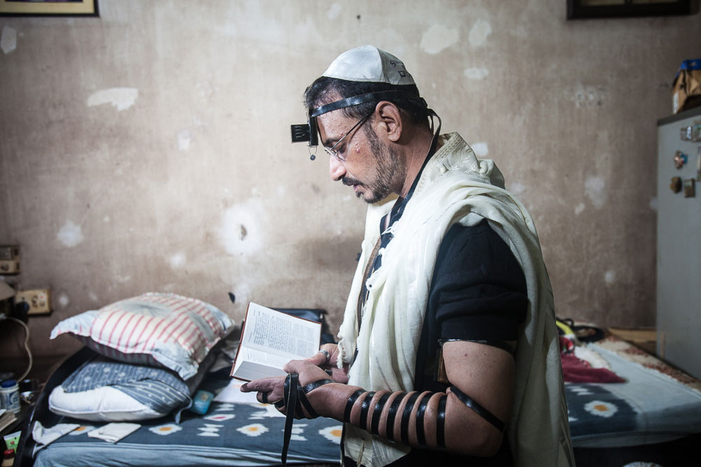 Shalom Israel, the former caretaker of Beth El Synagogue and undertaker of the Jewish cemetery, wearing the Tefillin during a weekday morning prayer in August 2014. He left Calcutta for Israel that December.