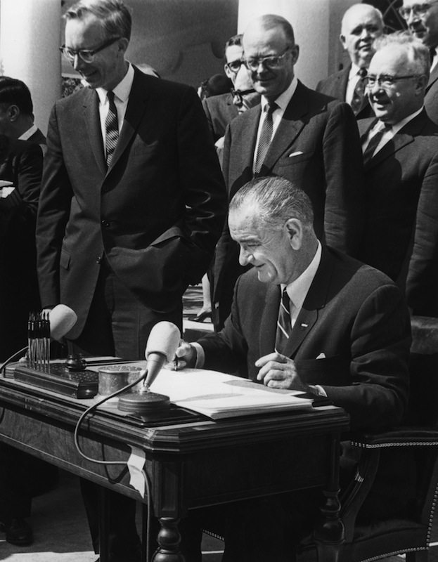 American president Lyndon B Johnson signs the war on poverty bill during a ceremony outdoors at the White House Rose Garden, Washington, DC., on Aug. 20, 1965