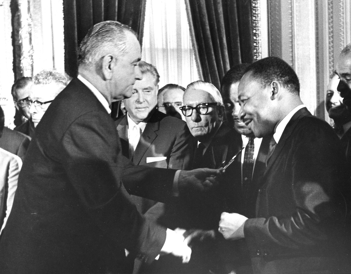 President Lyndon Johnson hands a souvenir pen to the Reverend Martin Luther King Jr after signing the Voting Rights Bill at the US Capital, Washington DC, in 1965.