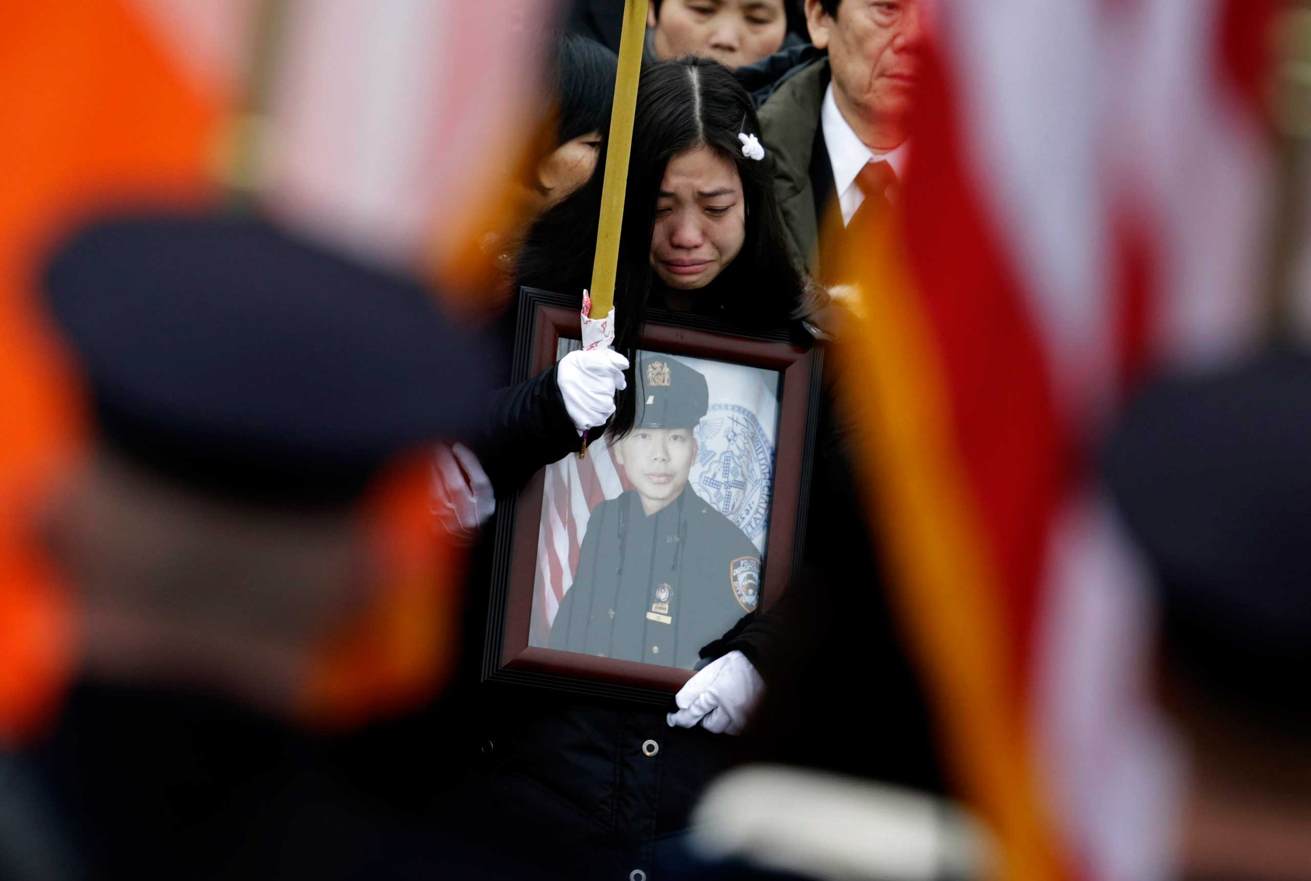 Widow Pei Xia Chen holds a photo of slain New York Police Department officer Wenjian Liu as his casket departs his funeral in the Brooklyn borough of New York on Jan. 4, 2015.