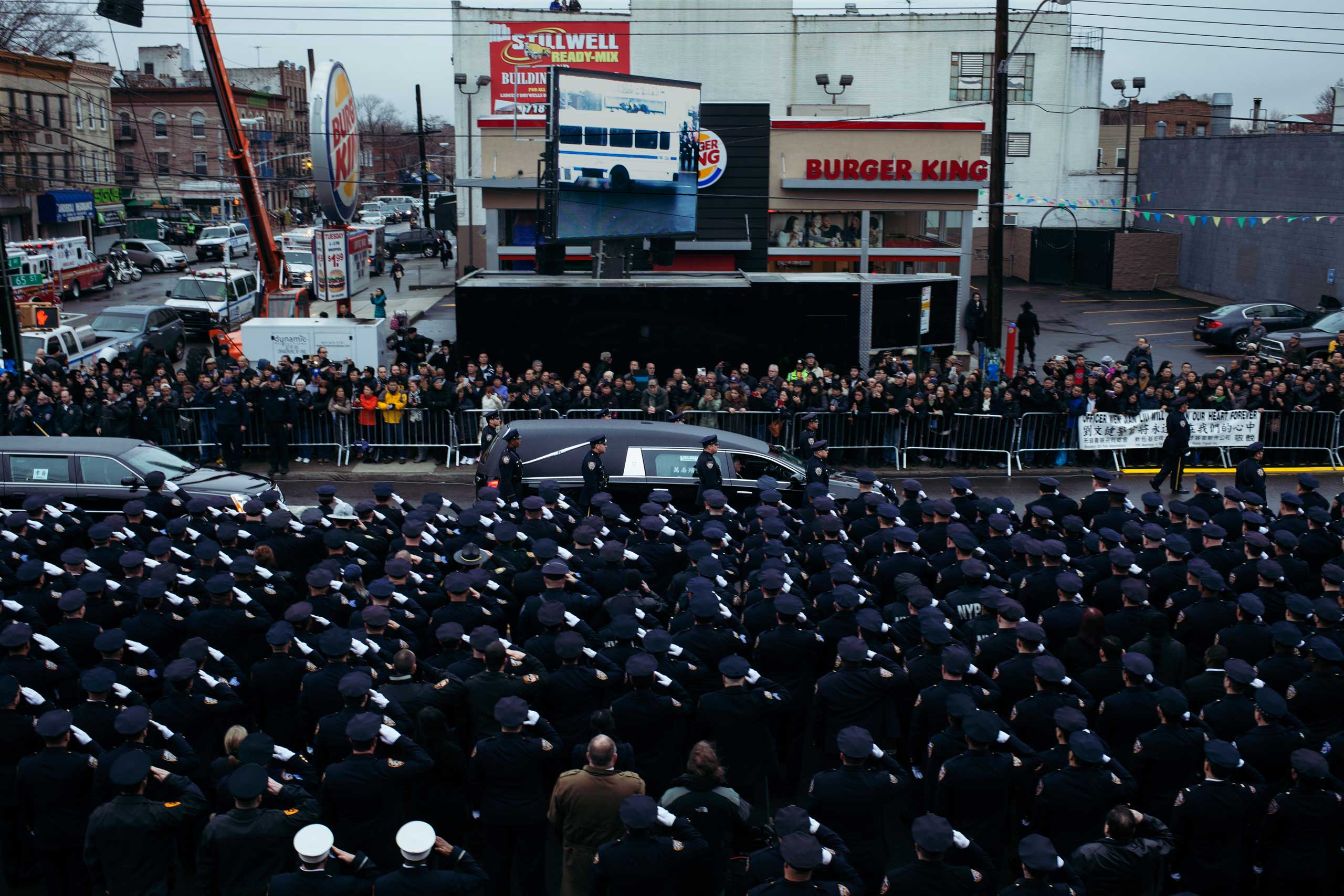 Law enforcement officers salute Officer Wenjian Liu as his hearse drives down 65th street in the Brooklyn borough of New York on Jan. 4, 2015.