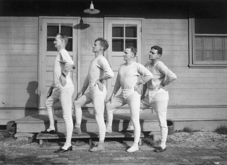 Four men wearing long underwear pose in a profile lineup, circa 1915.