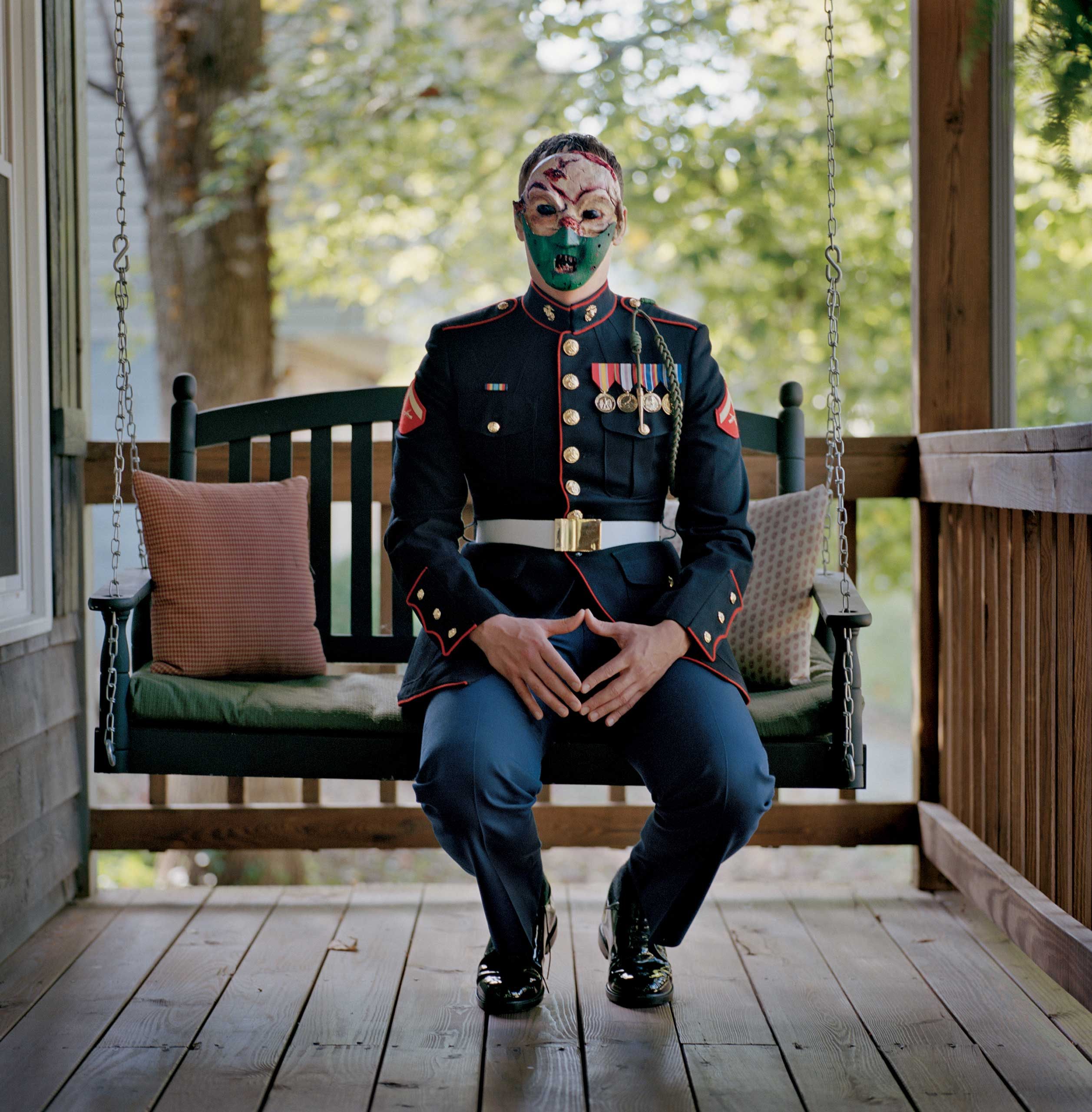 """From the January issue of National Geographic magazine: Healing Soldiers                               Marine Cpl. Chris McNair (Ret.)                               Afghanistan 2011-12                               Impeccable in his Marine uniform and outwardly composed, McNair sits on the porch of his parents' home in Virginia, anonymous behind a mask he made                               in an art therapy session. """"I was just going through pictures, and I saw the mask of Hannibal Lecter, and I thought, 'That's who I am' … He's probably dangerous, and that's who I felt I was. I had this muzzle on with all these wounds, and I couldn't tell anyone about them. I couldn't express my feelings."""""""