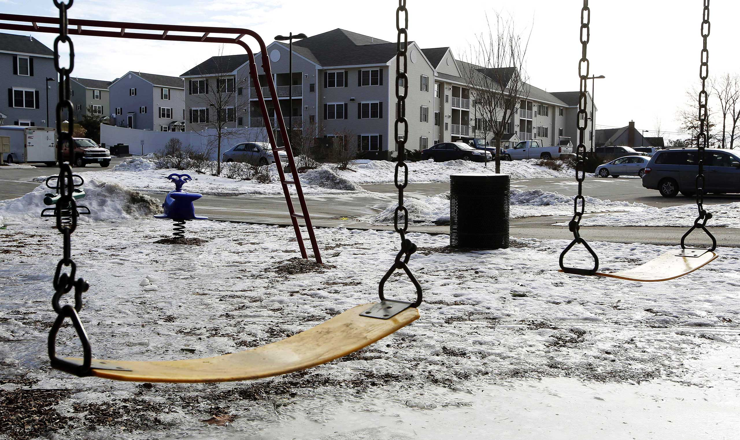 An empty playground is seen at an apartment complex,  Jan. 22, 2015, in Manchester, N.H. where authorities say twin 9-year-old boys were left mostly alone for four months after their parents took three siblings to Nigeria and left an uncle to care for them.