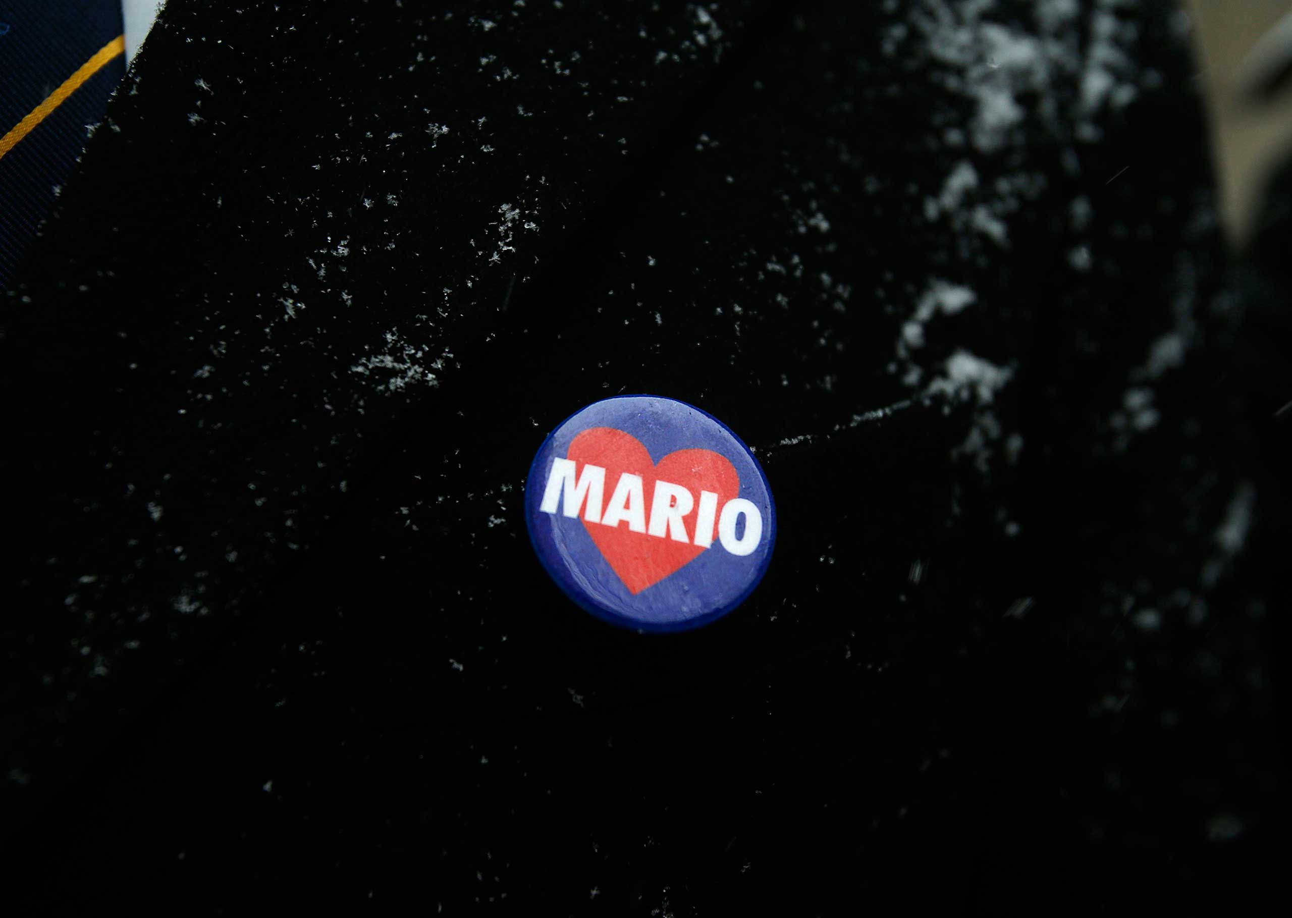 A mourner wears a Mario Cuomo button while waiting in line to enter St. Ignatius Loyola Church before the funeral service for the former New York governor in the Manhattan borough of New York on Jan. 6, 2015.