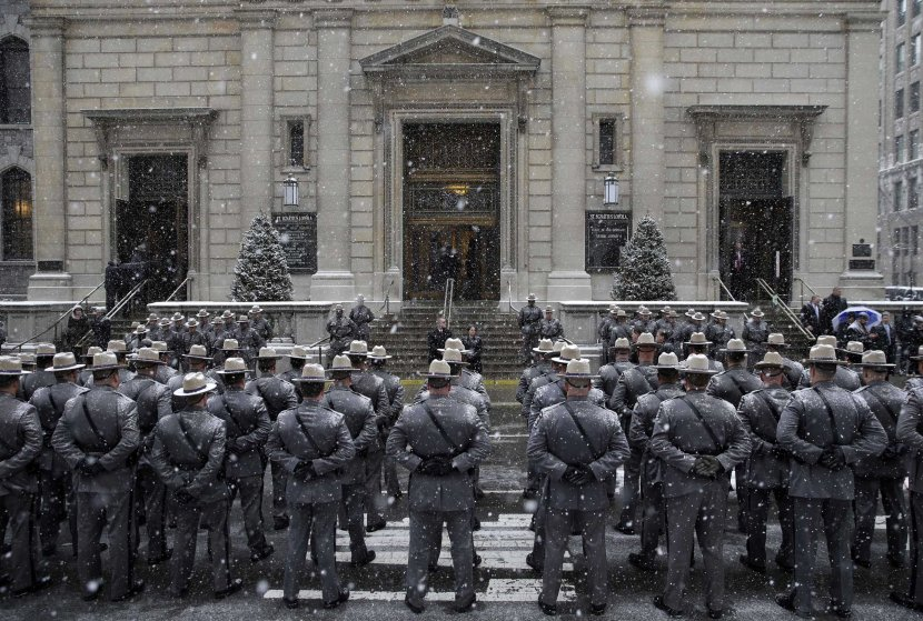 State troopers stand at attention in the snow before the funeral for former New York governor Mario Cuomo at Church of St. Ignatius Loyola in New York on Jan. 6, 2015.