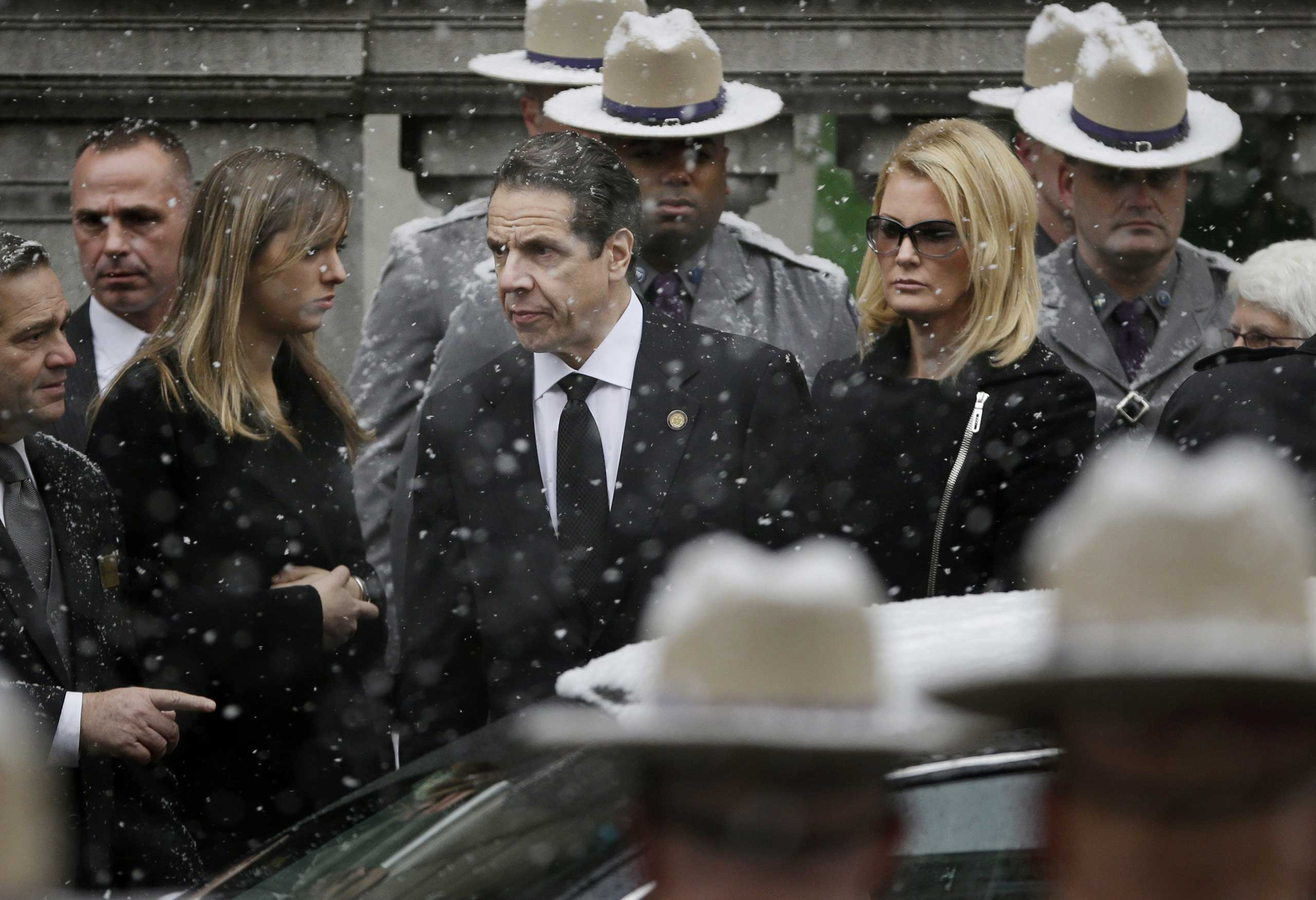 New York Governor Andrew Cuomo, center, waits with his girlfriend Sandra Lee while the body of his father, Mario Cuomo, is carried into Church of St. Ignatius Loyola for his funeral in New York, Tuesday, Jan. 6, 2015. Cuomo, 82, died in his Manhattan home on Jan. 1, hours after his son was inaugurated for a second term. (AP Photo/Seth Wenig)