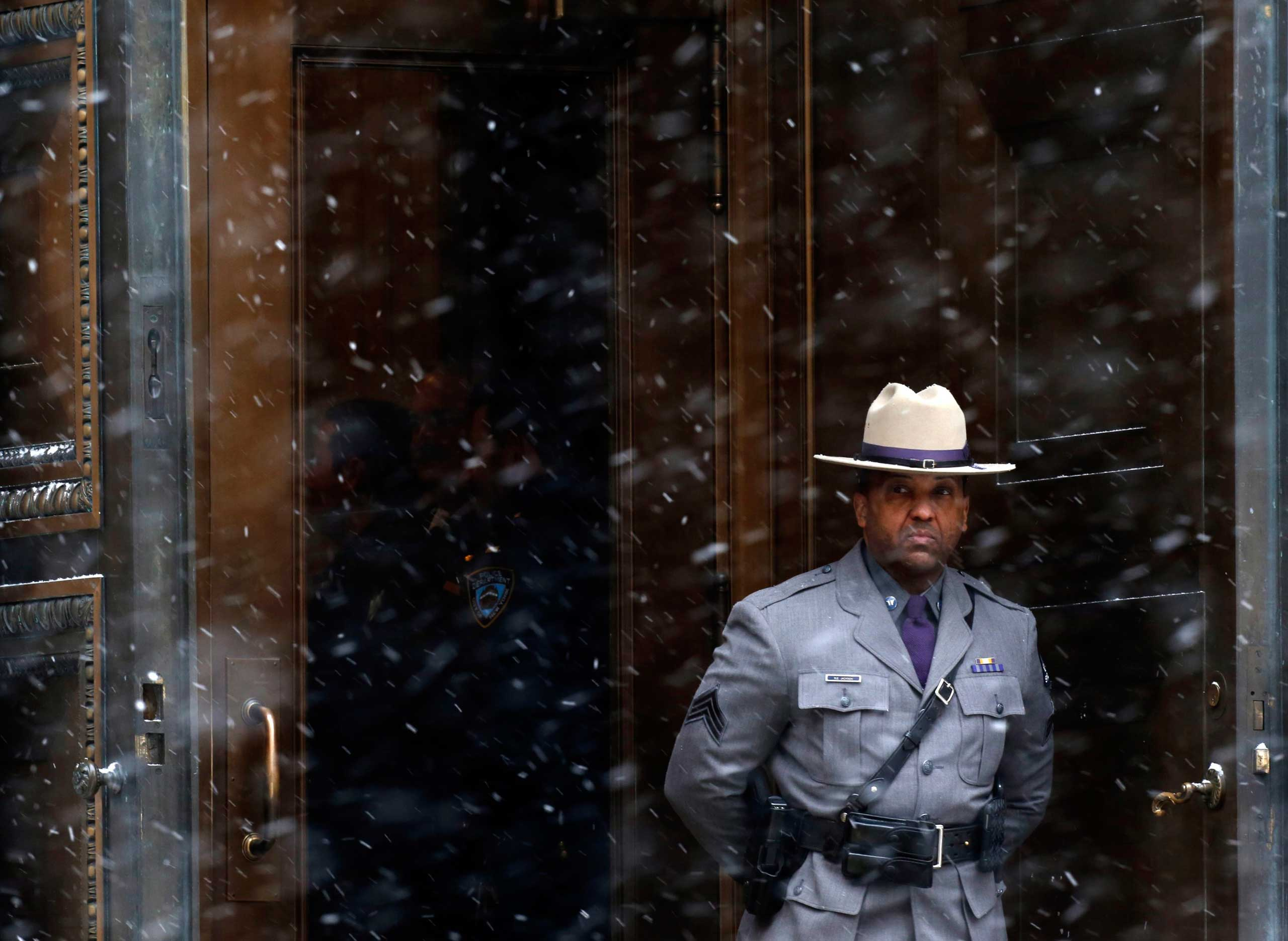 A New York State Police Trooper stands in the doorway outside St. Ignatius Loyola Church during the funeral service for former New York Governor Mario Cuomo in the Manhattan borough of New York, January 6, 2015. Cuomo, the three-time governor of New York and a leading voice of the Democratic Party's liberal wing who turned down several invitations to seek the U.S. presidency, died on January 1 at his home in Manhattan. He was 82. REUTERS/Carlo Allegri (UNITED STATES - Tags: POLITICS OBITUARY)